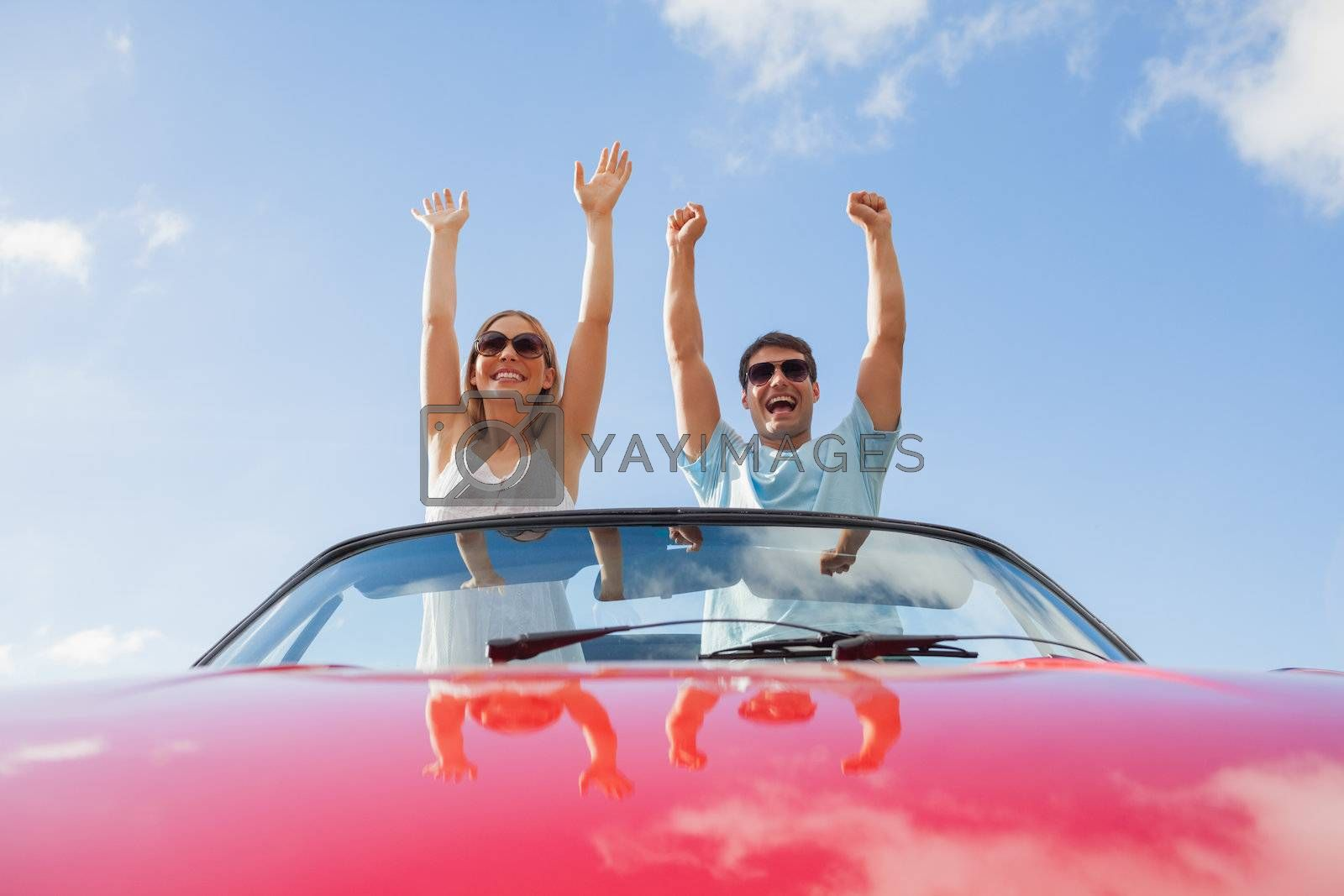 Crazy couple standing in red cabriolet by Wavebreakmedia