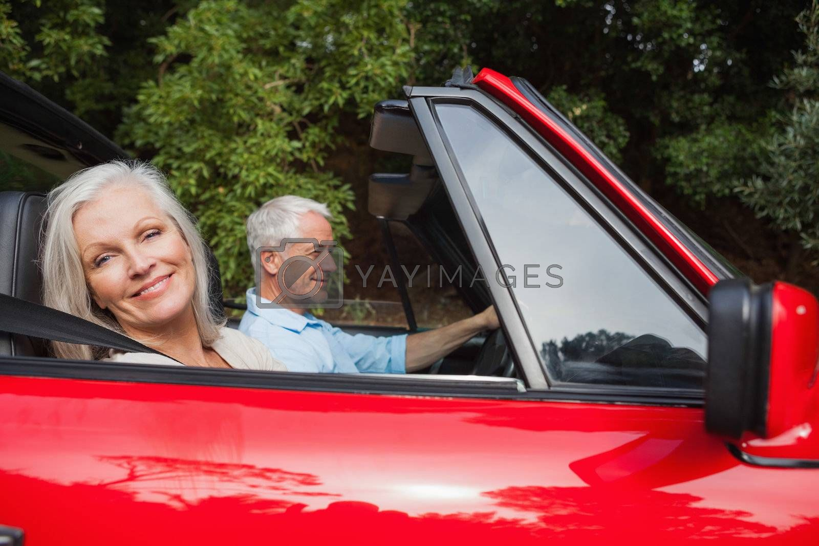 Side view of mature couple driving red convertible by Wavebreakmedia