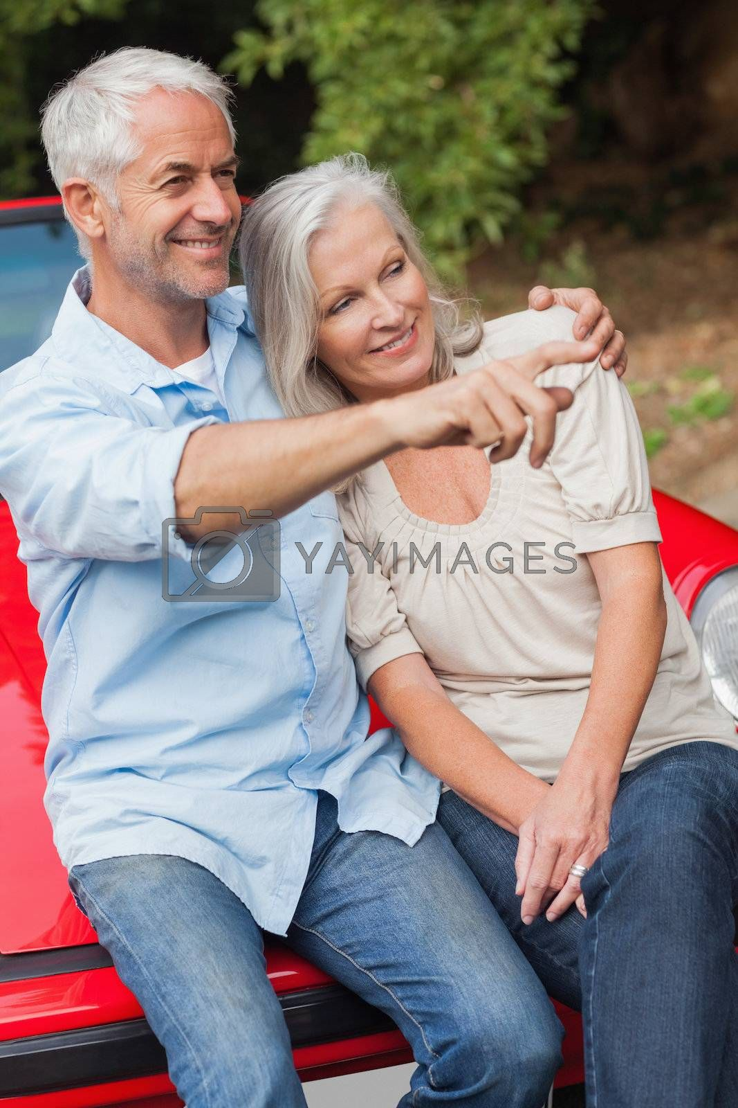 Smiling mature couple sitting on their red convertible by Wavebreakmedia