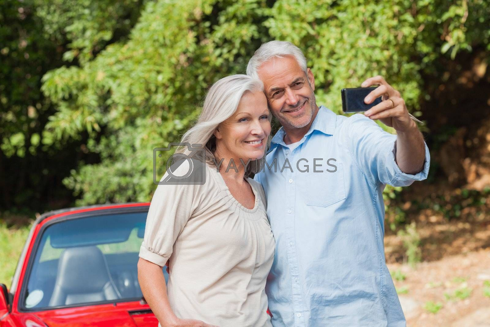 Cheerful mature couple taking pictures of themselves  by Wavebreakmedia