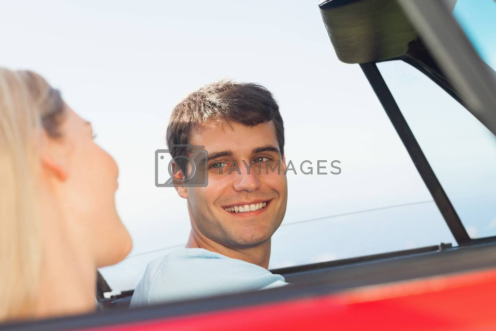 Smiling man looking at his pretty girlfriend while driving by Wavebreakmedia
