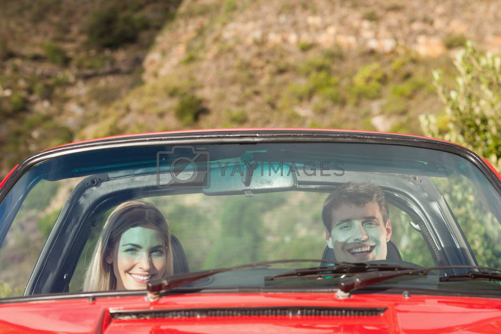 Front view of smiling couple in red cabriolet by Wavebreakmedia