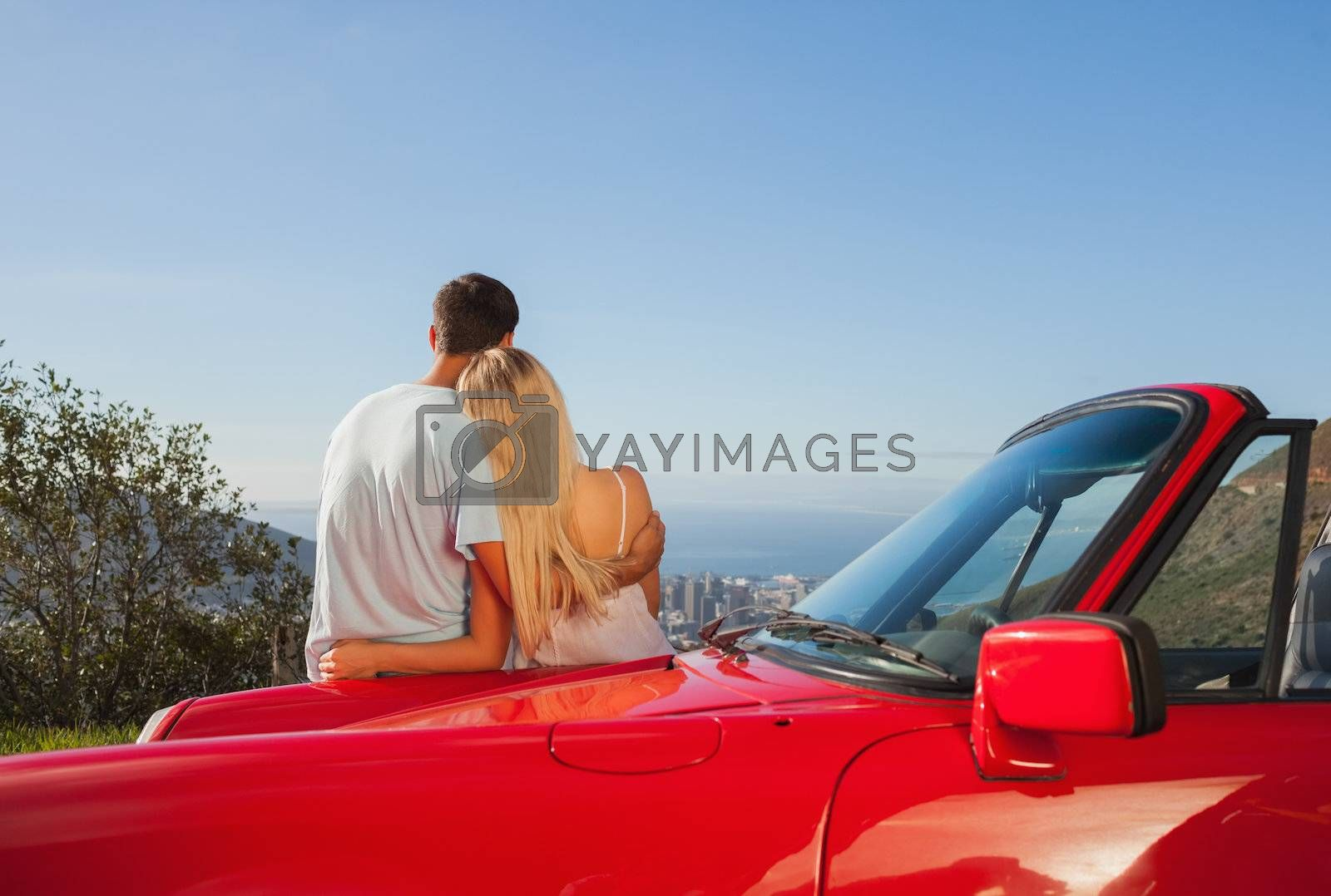 Rear view of couple hugging and admiring panorama by Wavebreakmedia