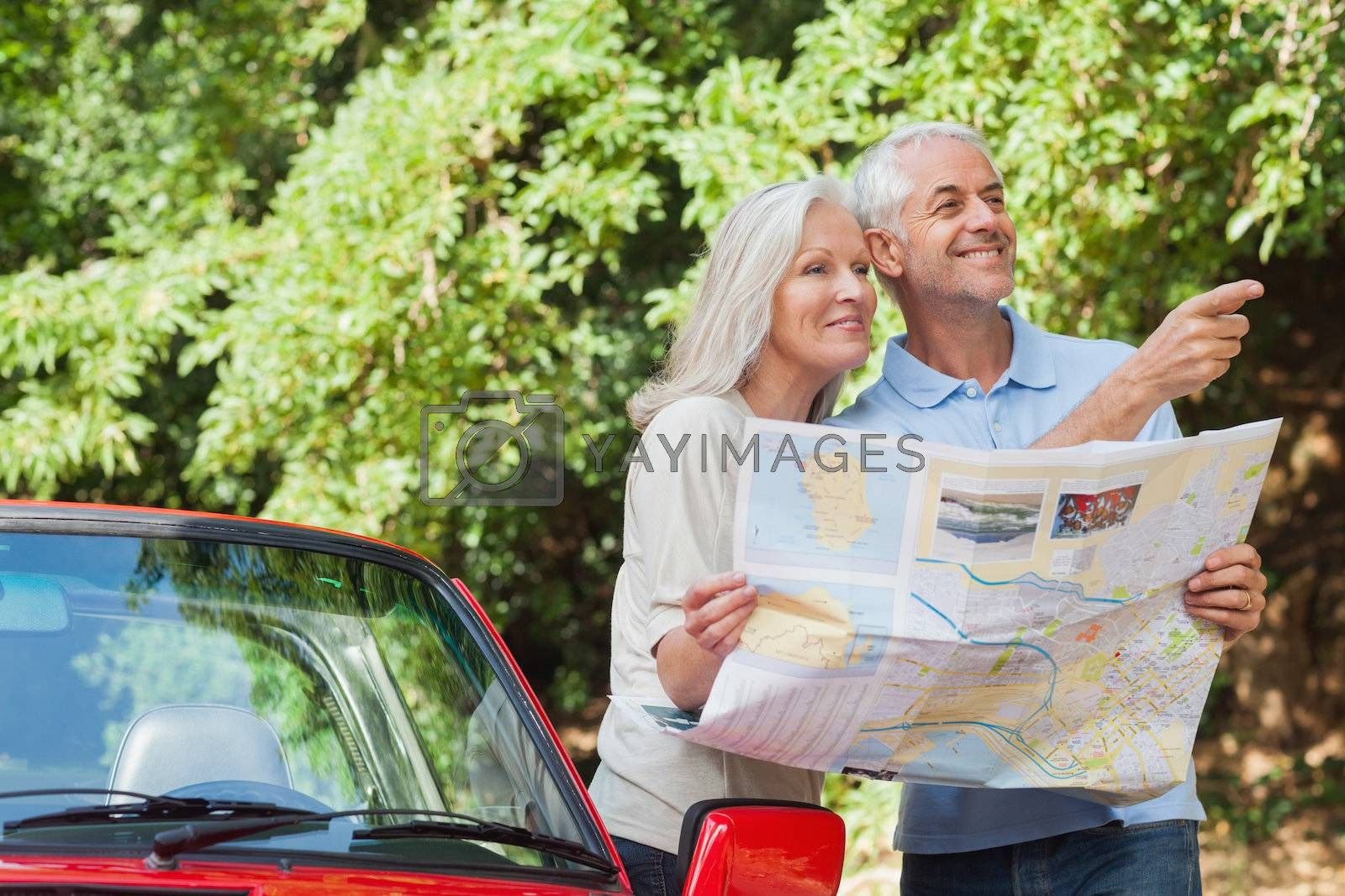 Cheerful mature couple reading map looking for direction by Wavebreakmedia