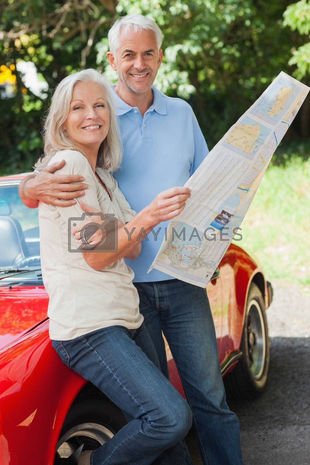 Happy mature couple reading map together by Wavebreakmedia