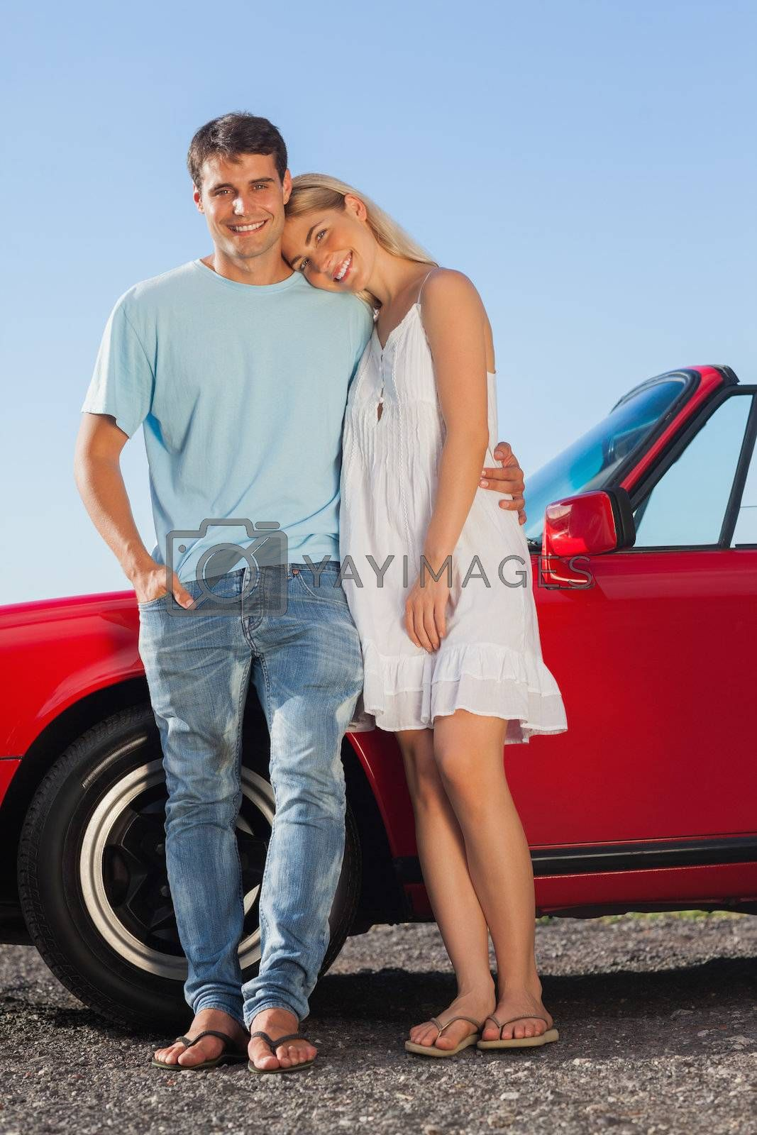 Happy cute couple posing against their red cabriolet by Wavebreakmedia