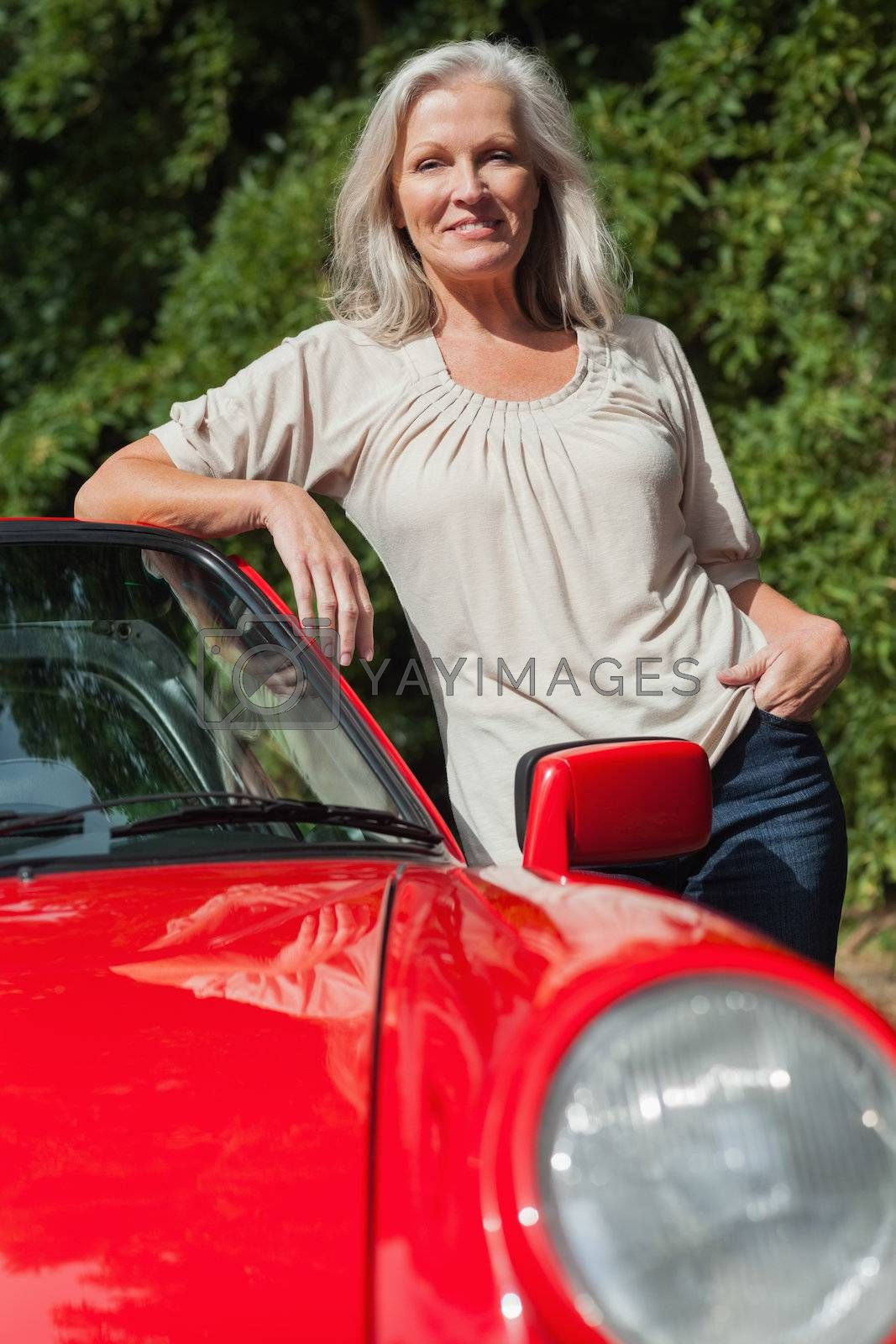 Smiling mature woman leaning against her red cabriolet by Wavebreakmedia