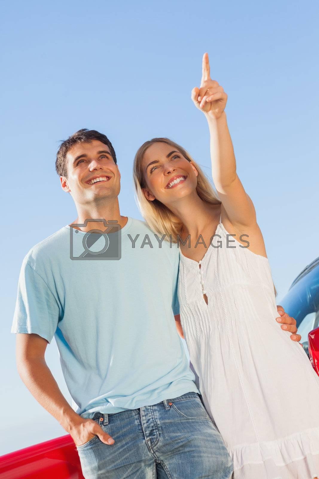 Happy woman showing something to her handsome boyfriend by Wavebreakmedia