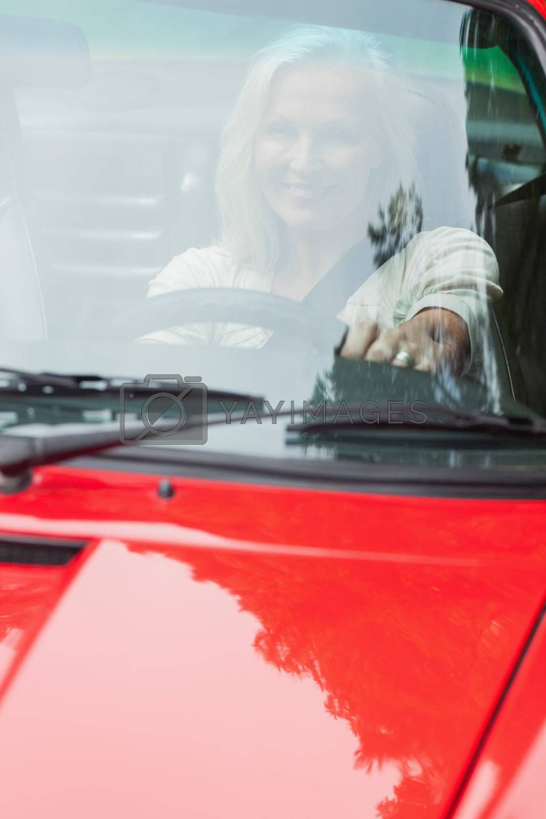 Smiling mature woman driving red cabriolet by Wavebreakmedia