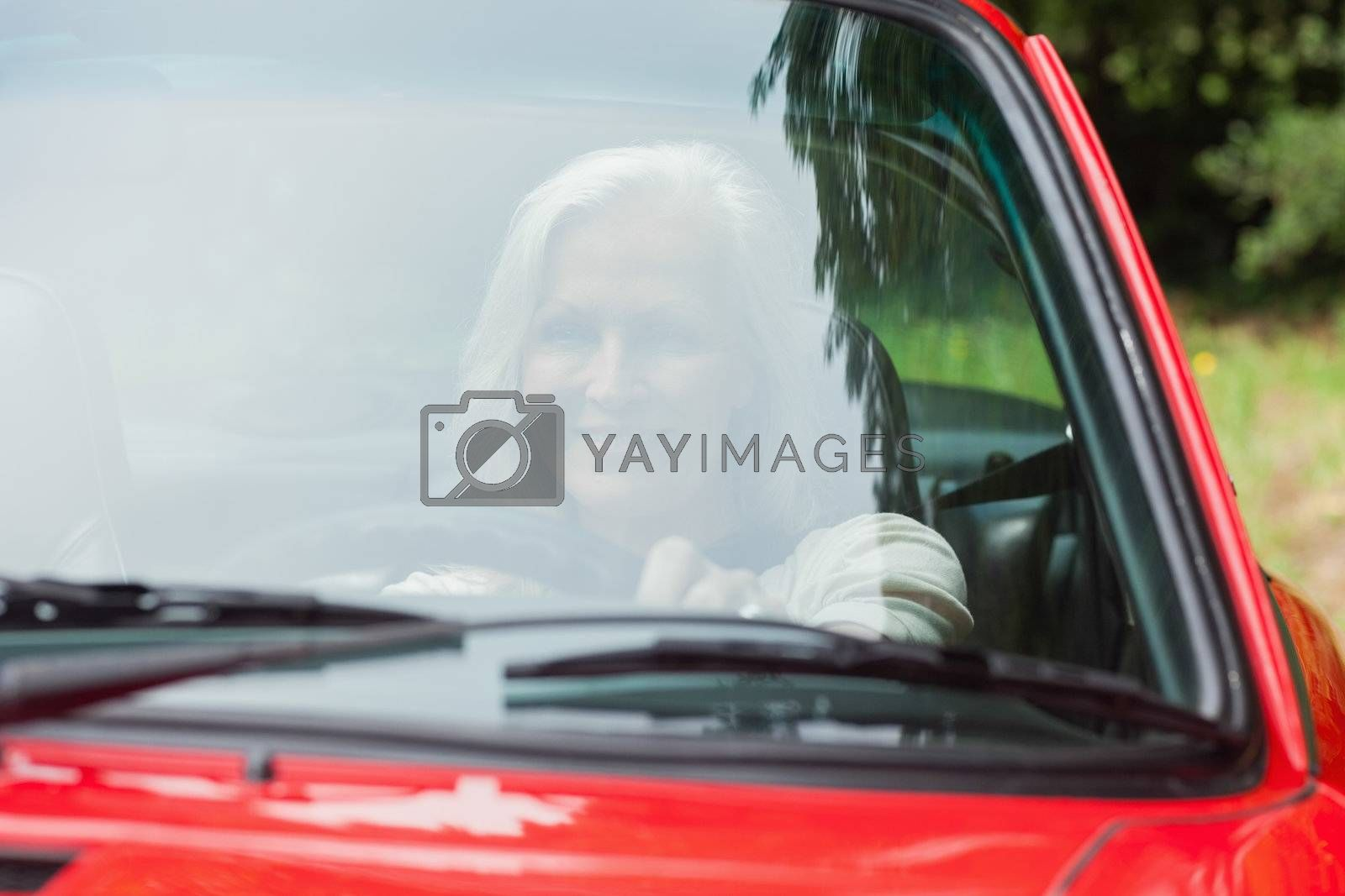 Cheerful mature woman driving red cabriolet by Wavebreakmedia