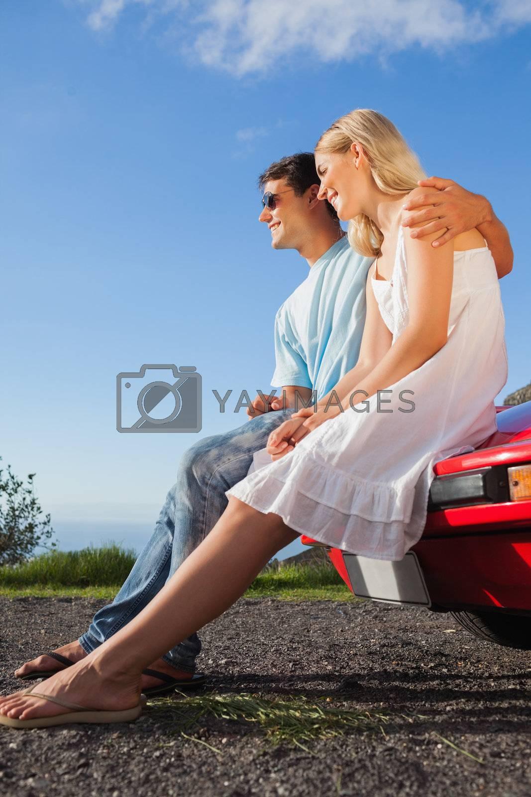 Cheerful couple sitting on their cabriolet car hood by Wavebreakmedia