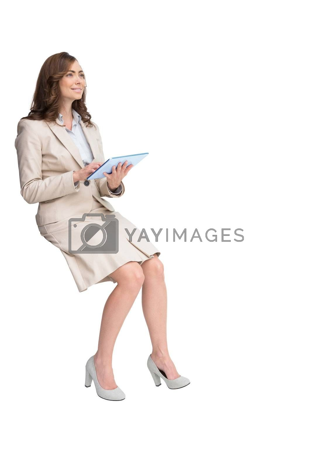 Businesswoman holding tablet and looking up by Wavebreakmedia