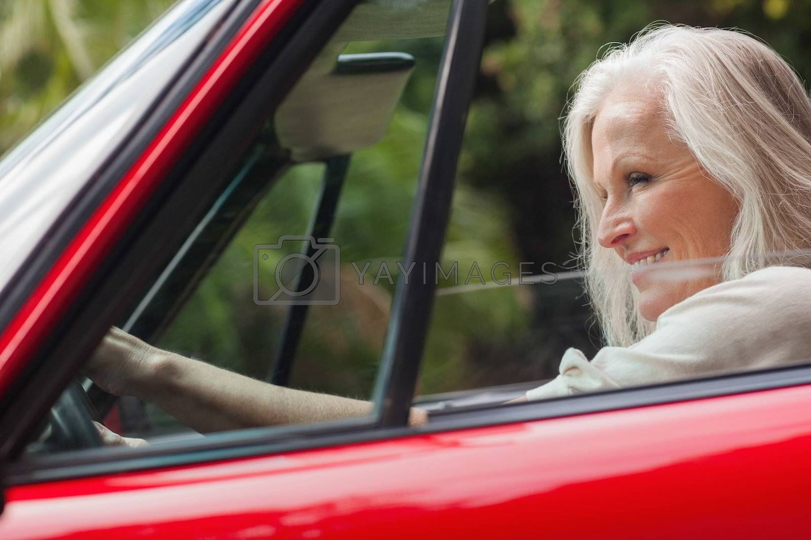 Cheerful mature woman driving red convertible by Wavebreakmedia