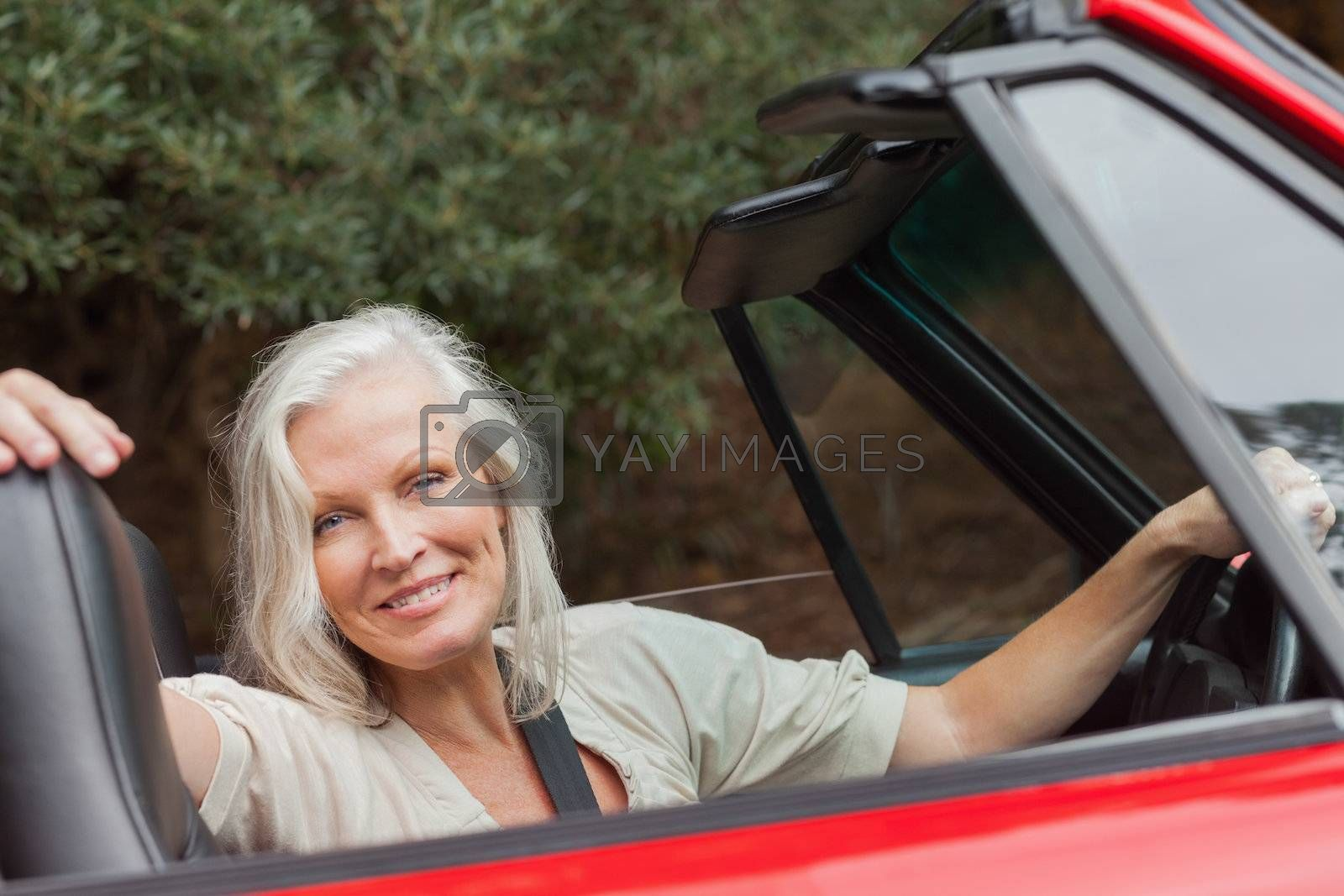 Smiling mature woman posing in red convertible by Wavebreakmedia
