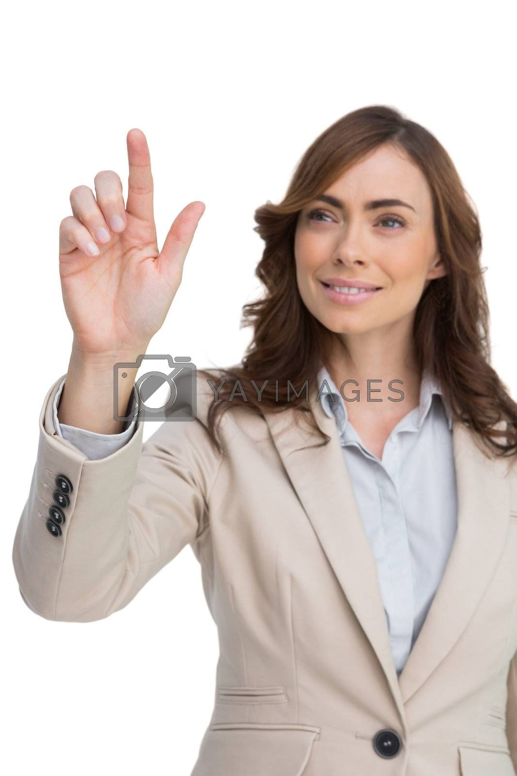 Young businesswoman touching invisible screen by Wavebreakmedia