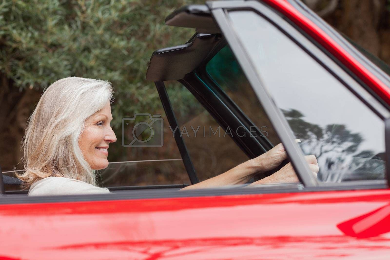Happy mature woman driving red convertible by Wavebreakmedia