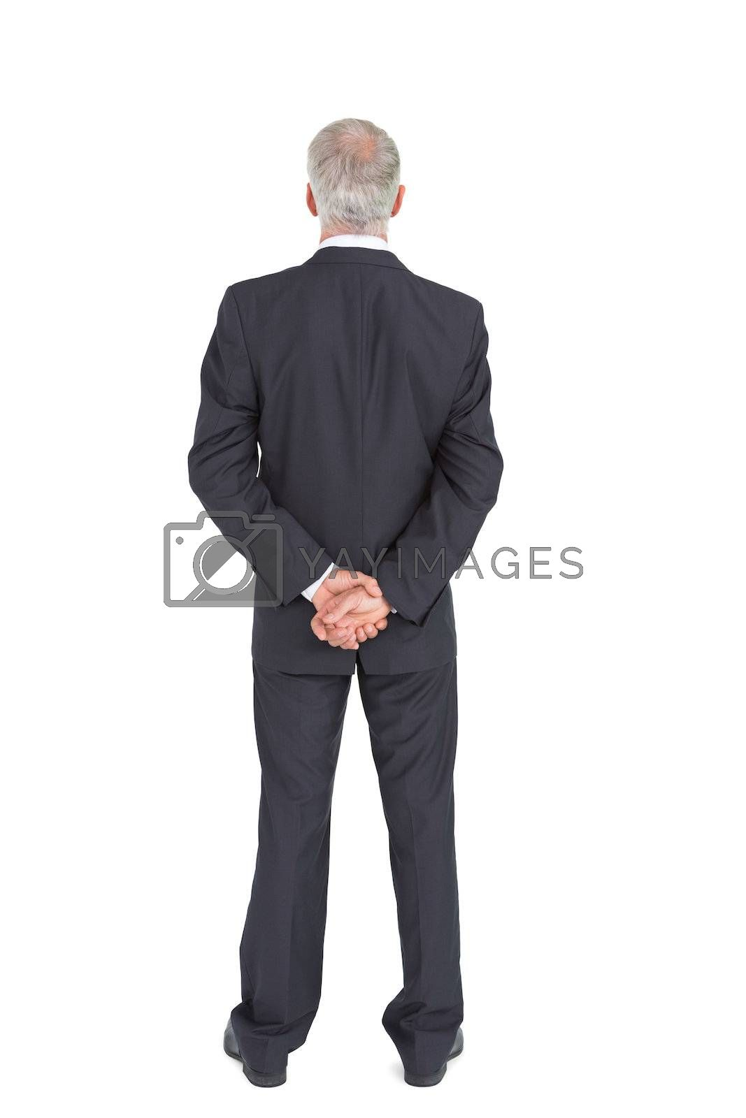 Rear view of serious businessman posing by Wavebreakmedia