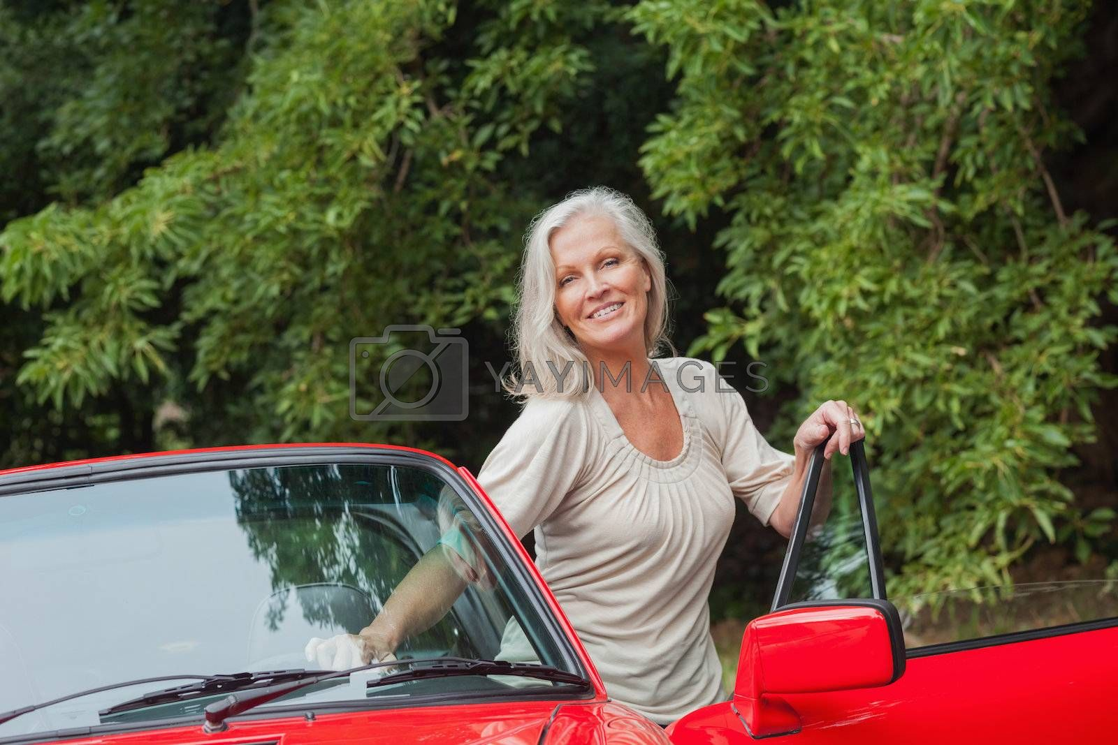 Cheerful mature woman getting off her convertible by Wavebreakmedia