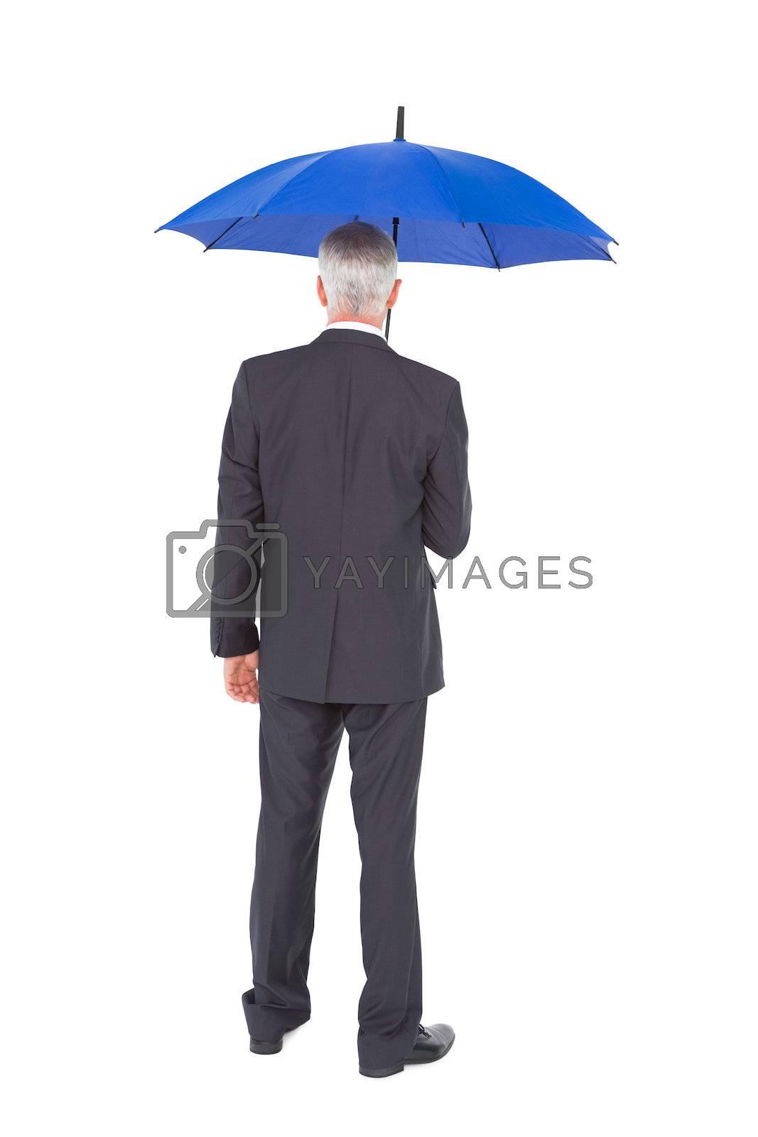 Rear view of mature businessman holding blue umbrella by Wavebreakmedia