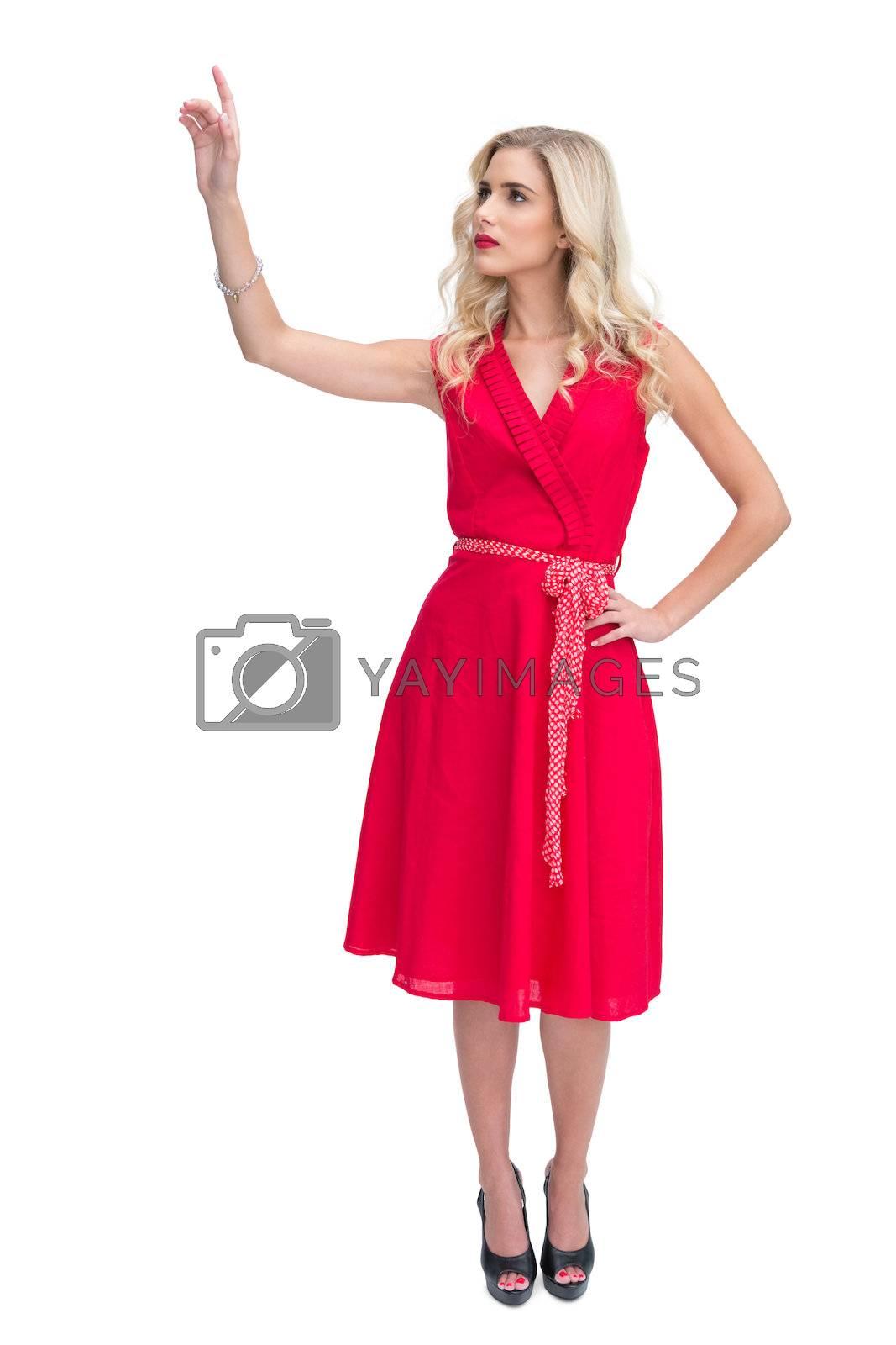 Cheerful woman in red dress waving by Wavebreakmedia
