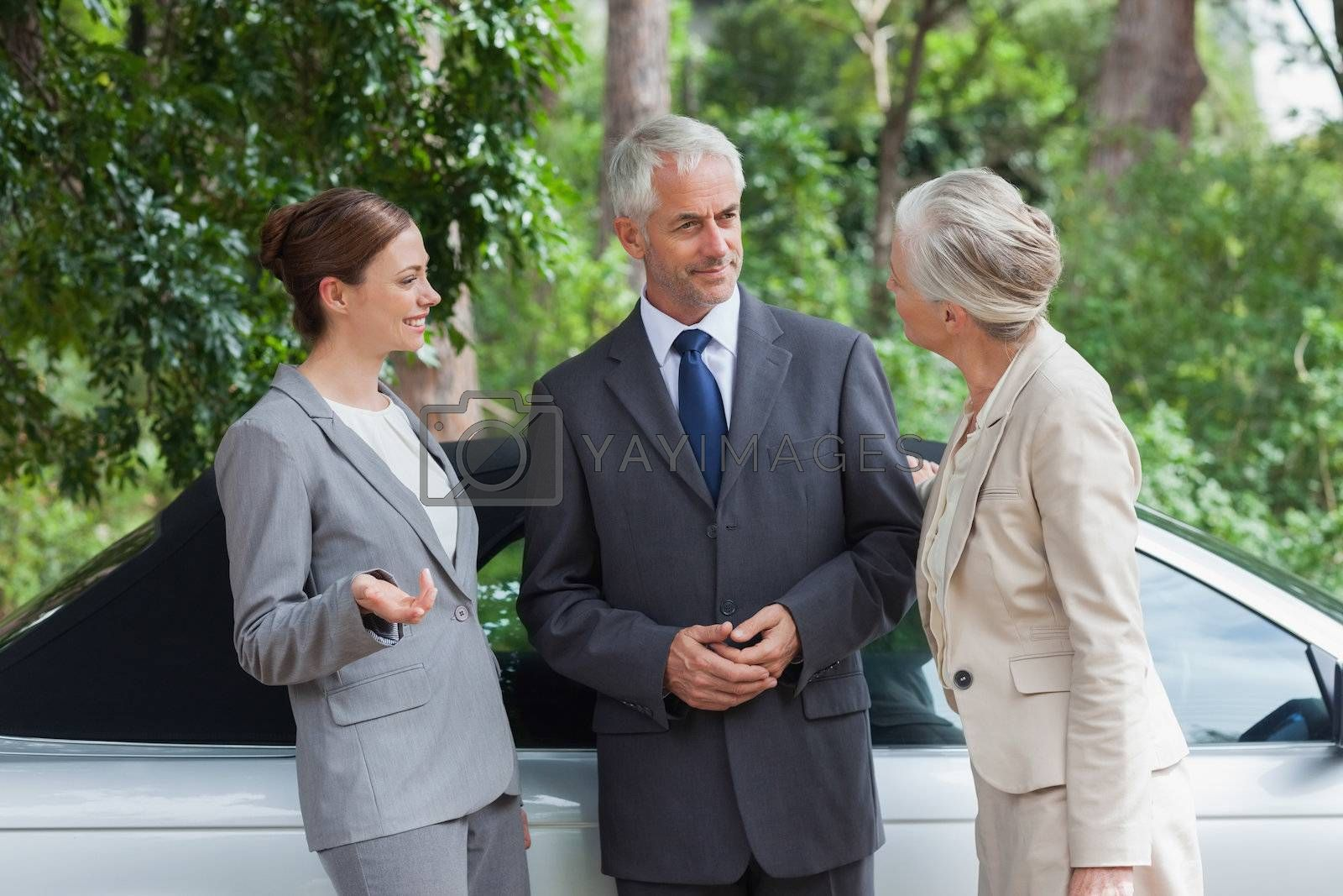 Smiling business people talking together by classy cabriolet by Wavebreakmedia