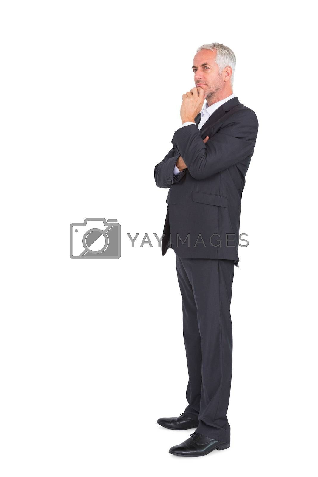 Mature thoughtful businessman crossing arms by Wavebreakmedia