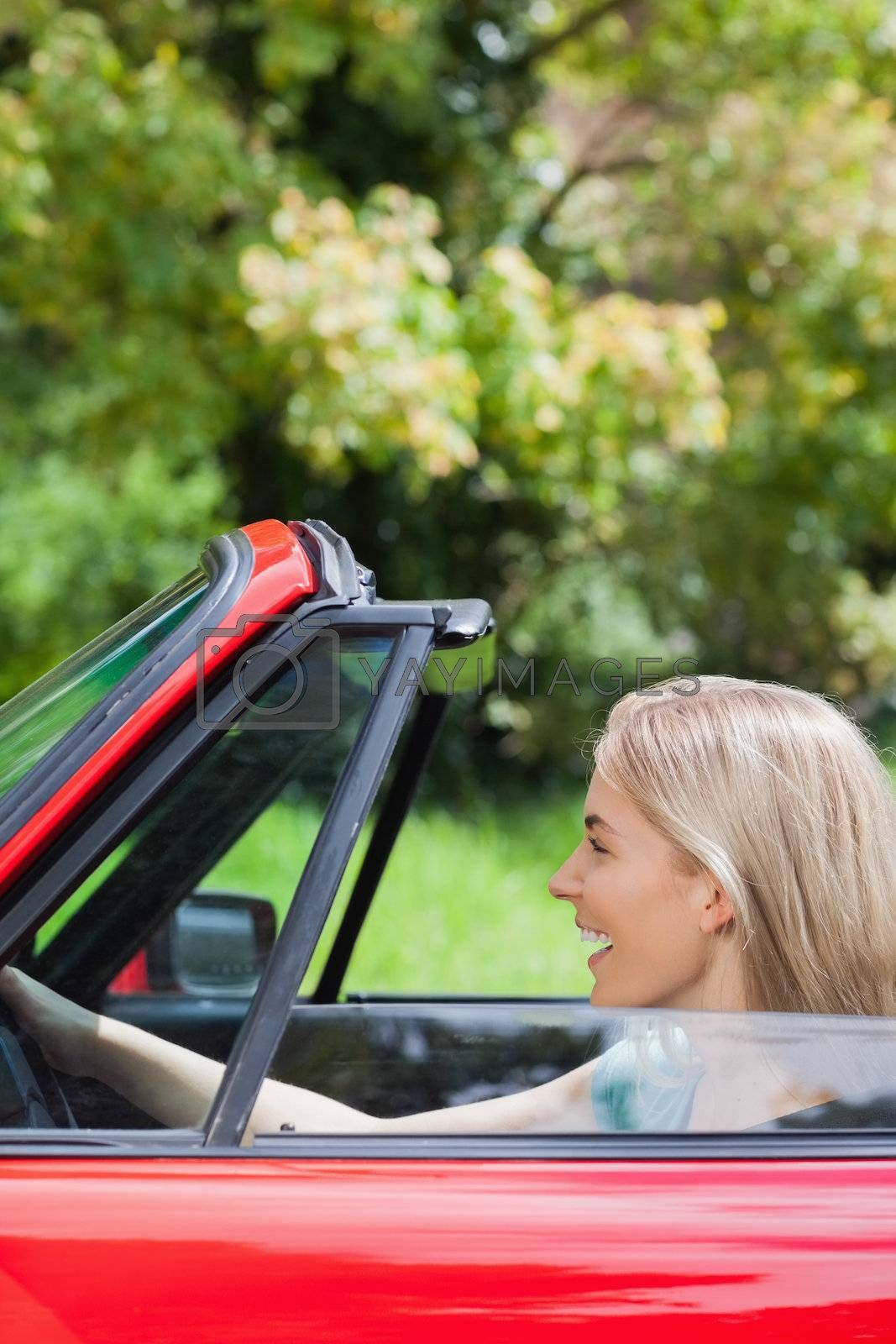 Happy woman driving red cabriolet by Wavebreakmedia