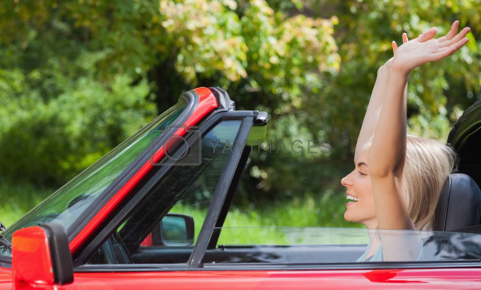 Happy blonde woman enjoying her red cabriolet by Wavebreakmedia