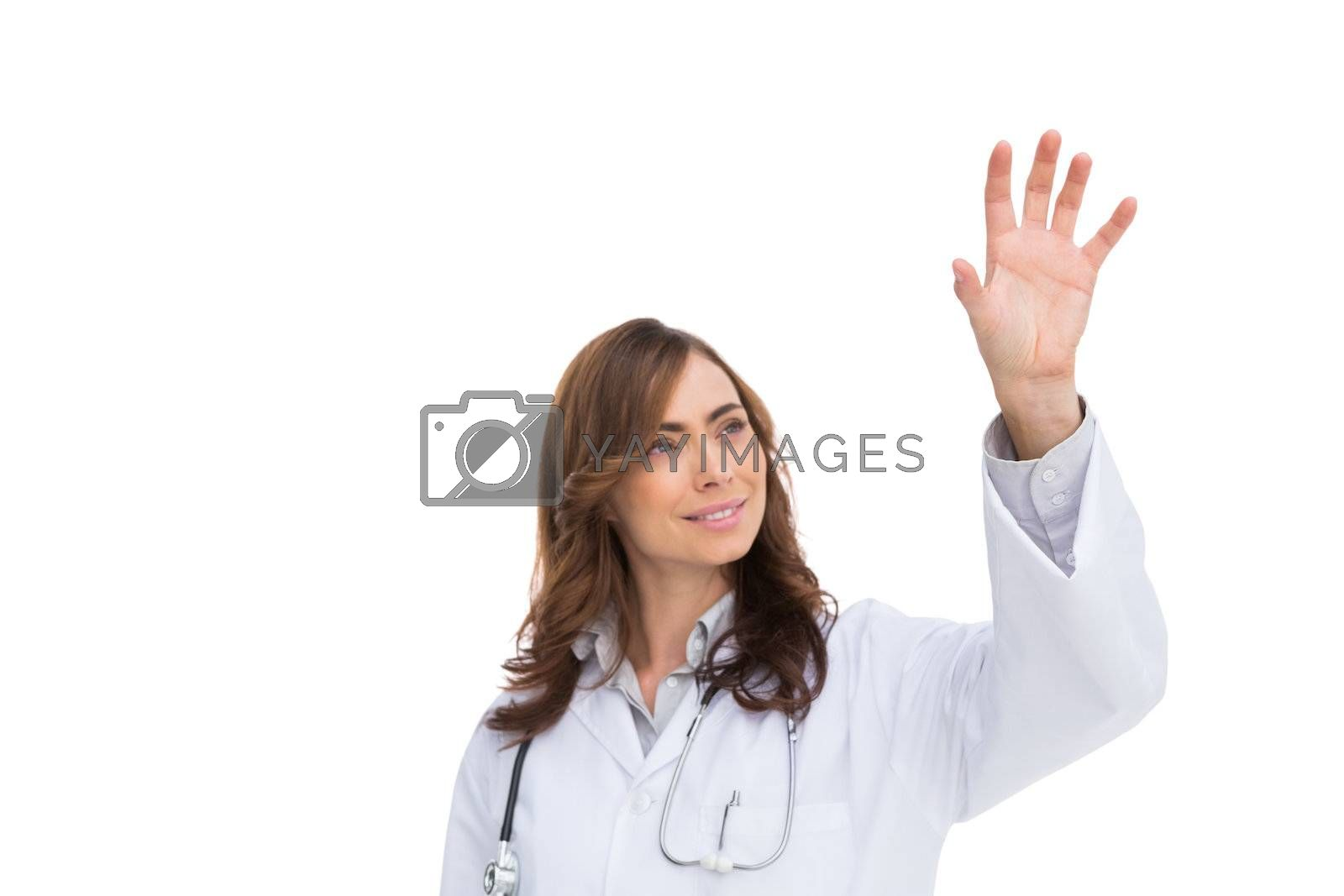 Brunette doctor reaching for something in the air by Wavebreakmedia