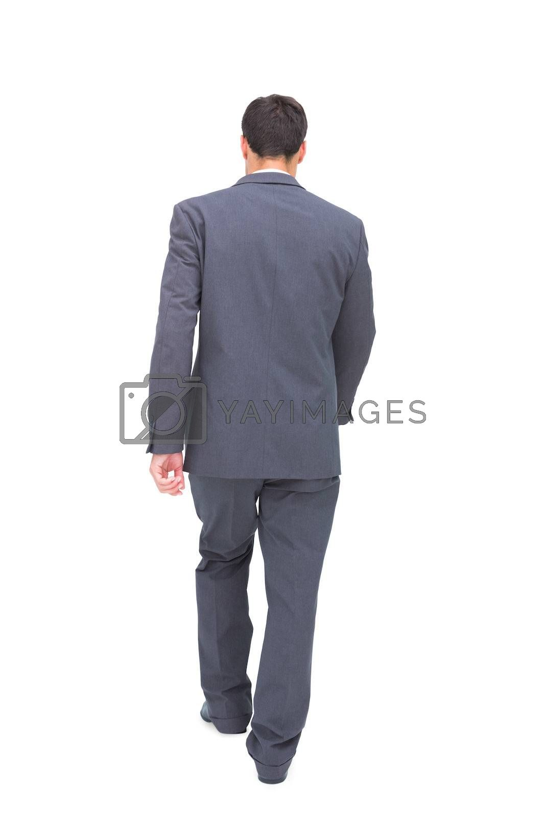 Young businessman walking away from camera by Wavebreakmedia