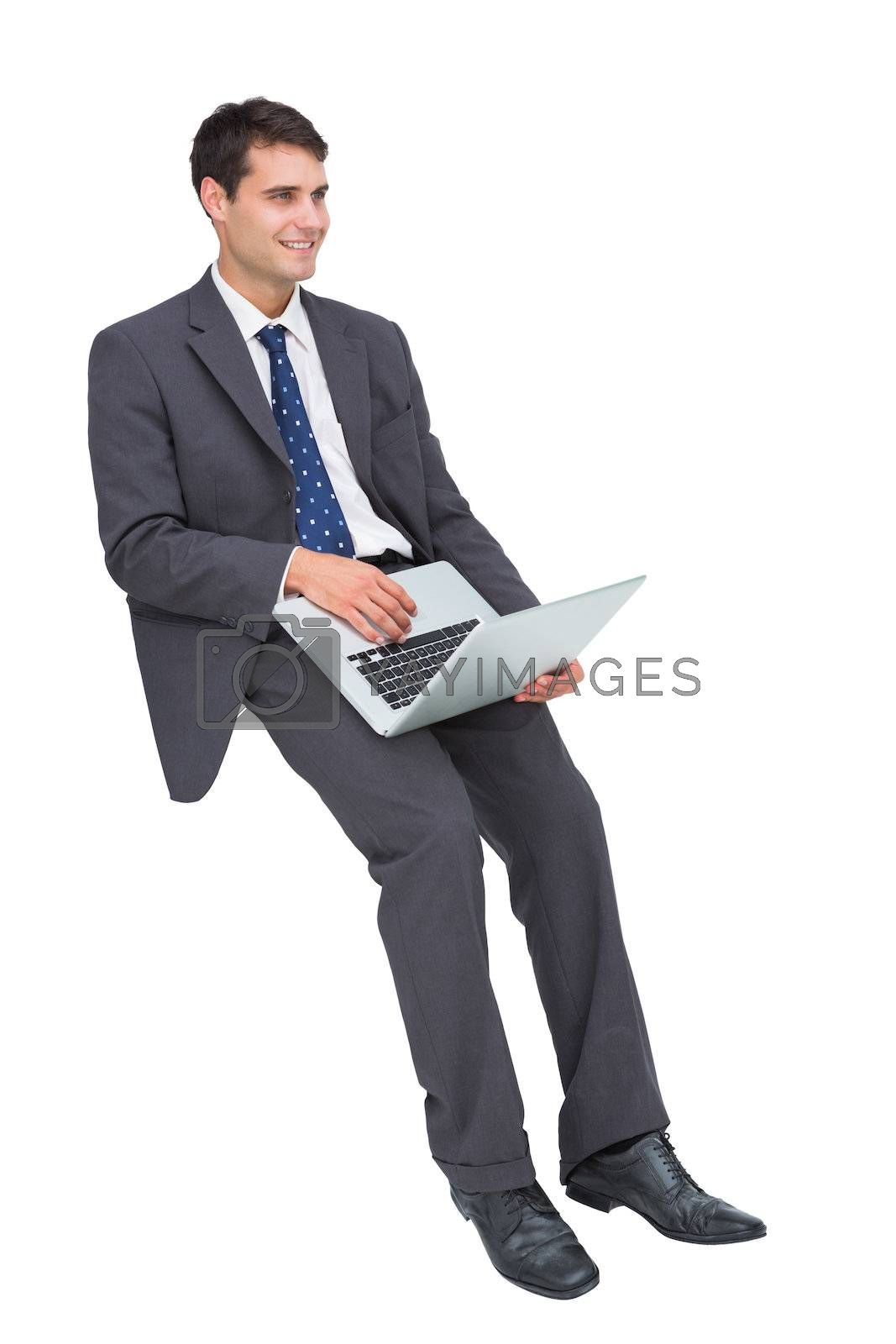 Smiling businessman sitting using a laptop  by Wavebreakmedia