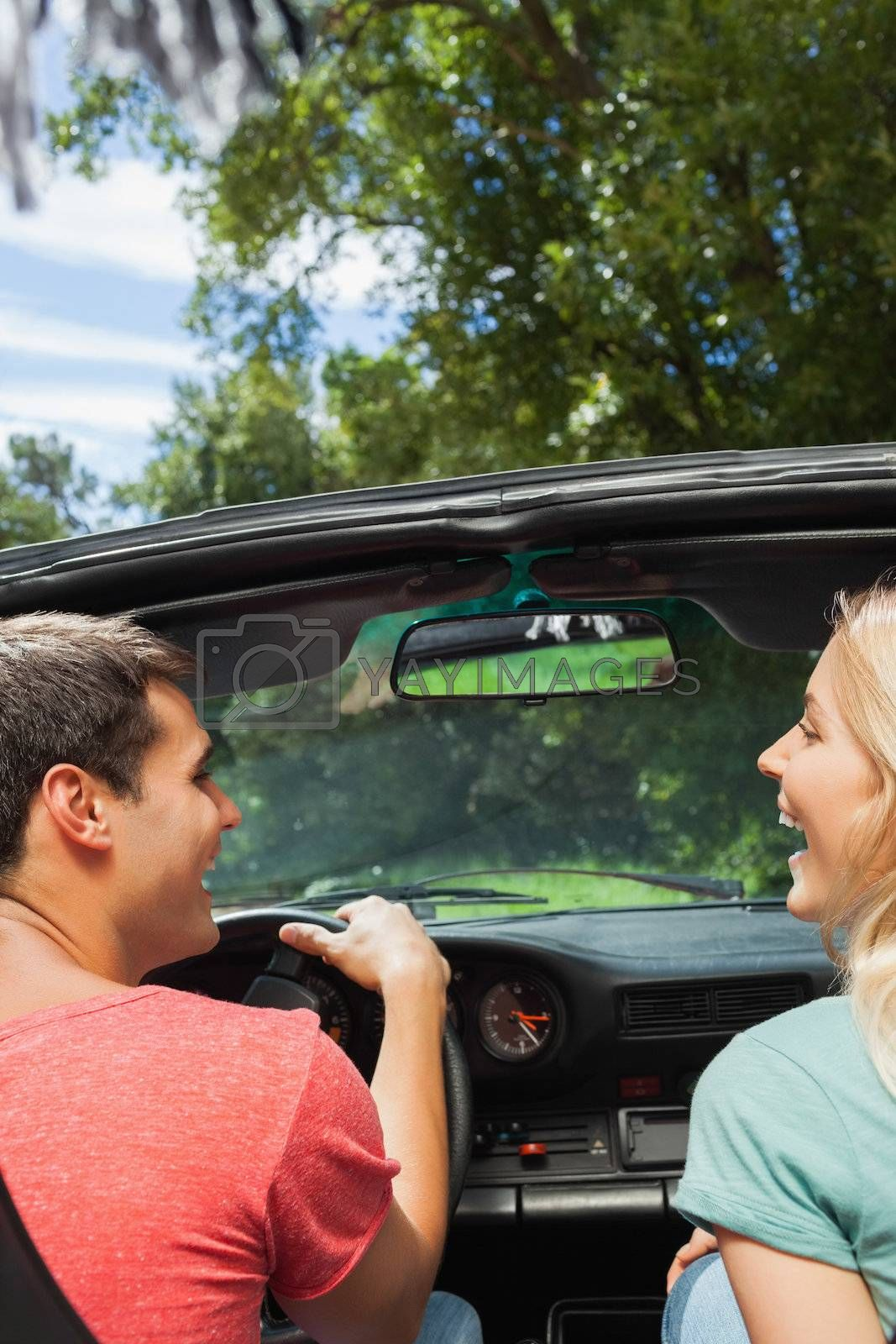 Rear view of cheerful couple in cabriolet by Wavebreakmedia