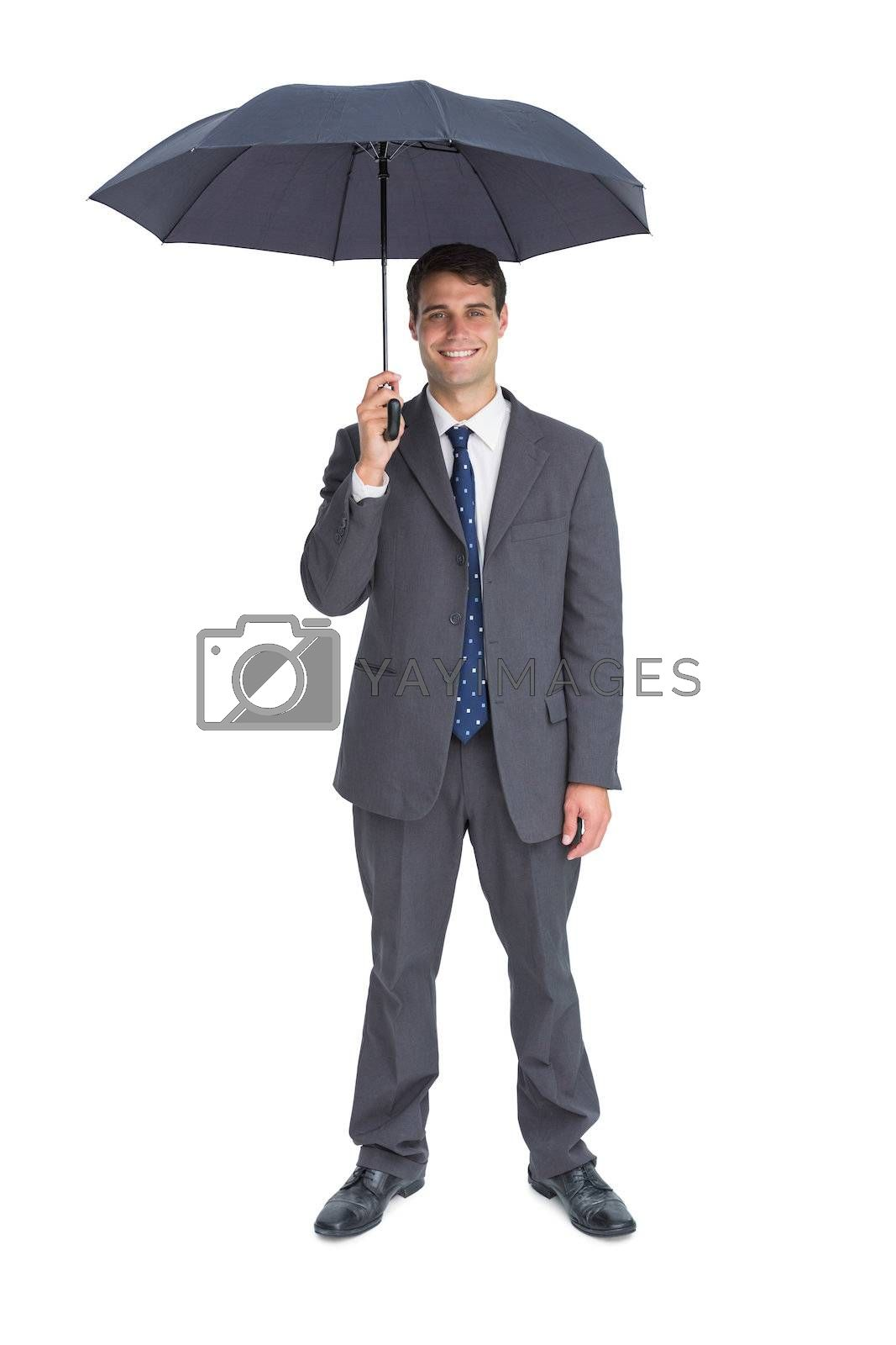 Happy businessman holding grey umbrella by Wavebreakmedia