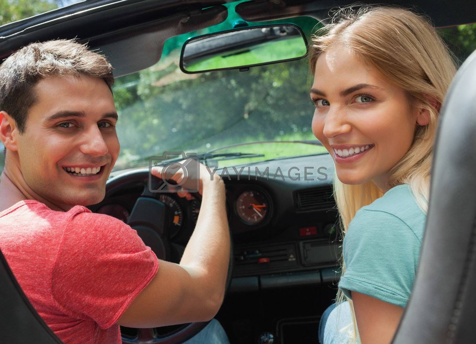 Cheerful couple looking at camera over shoulder by Wavebreakmedia