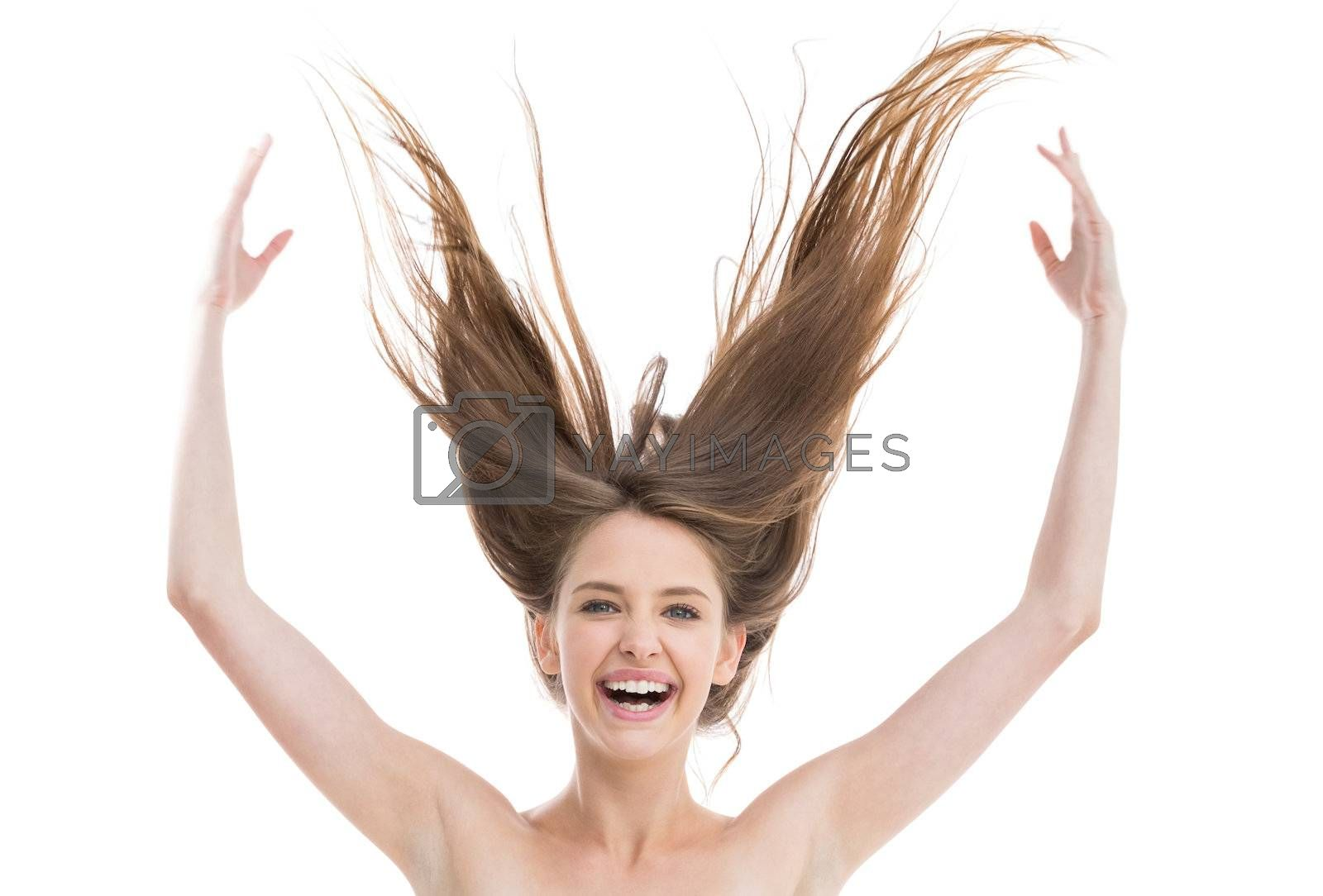 Laughing pretty woman throwing her hair up by Wavebreakmedia