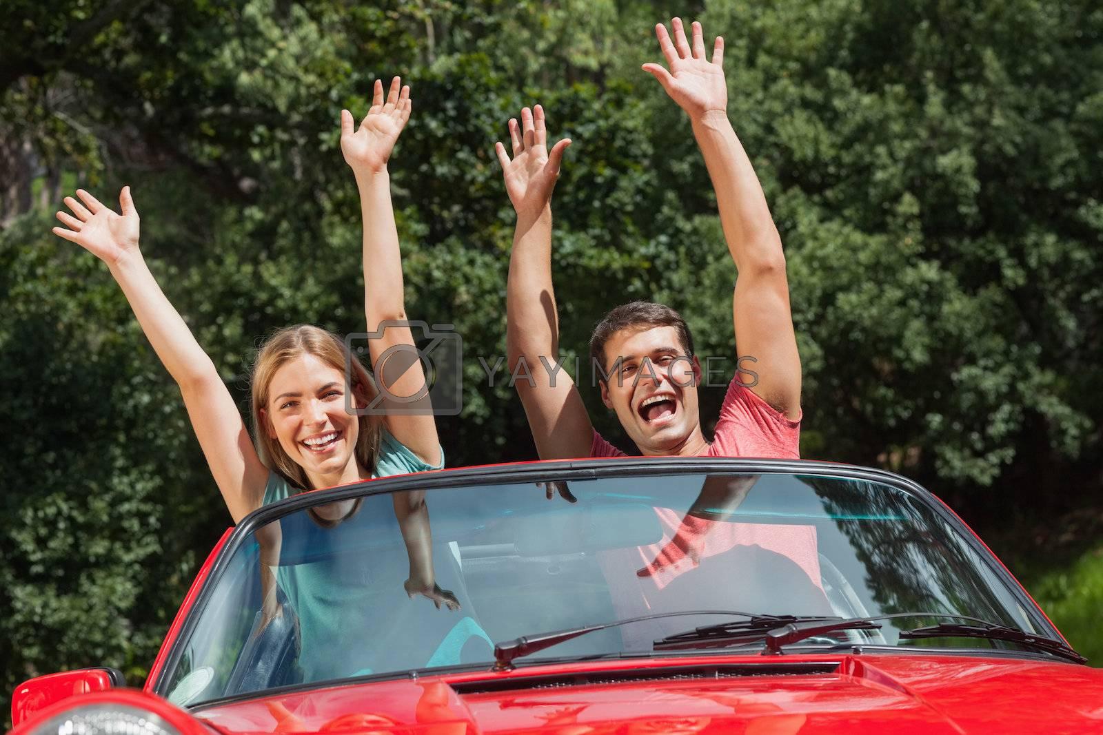 Happy couple having fun in their cabriolet by Wavebreakmedia
