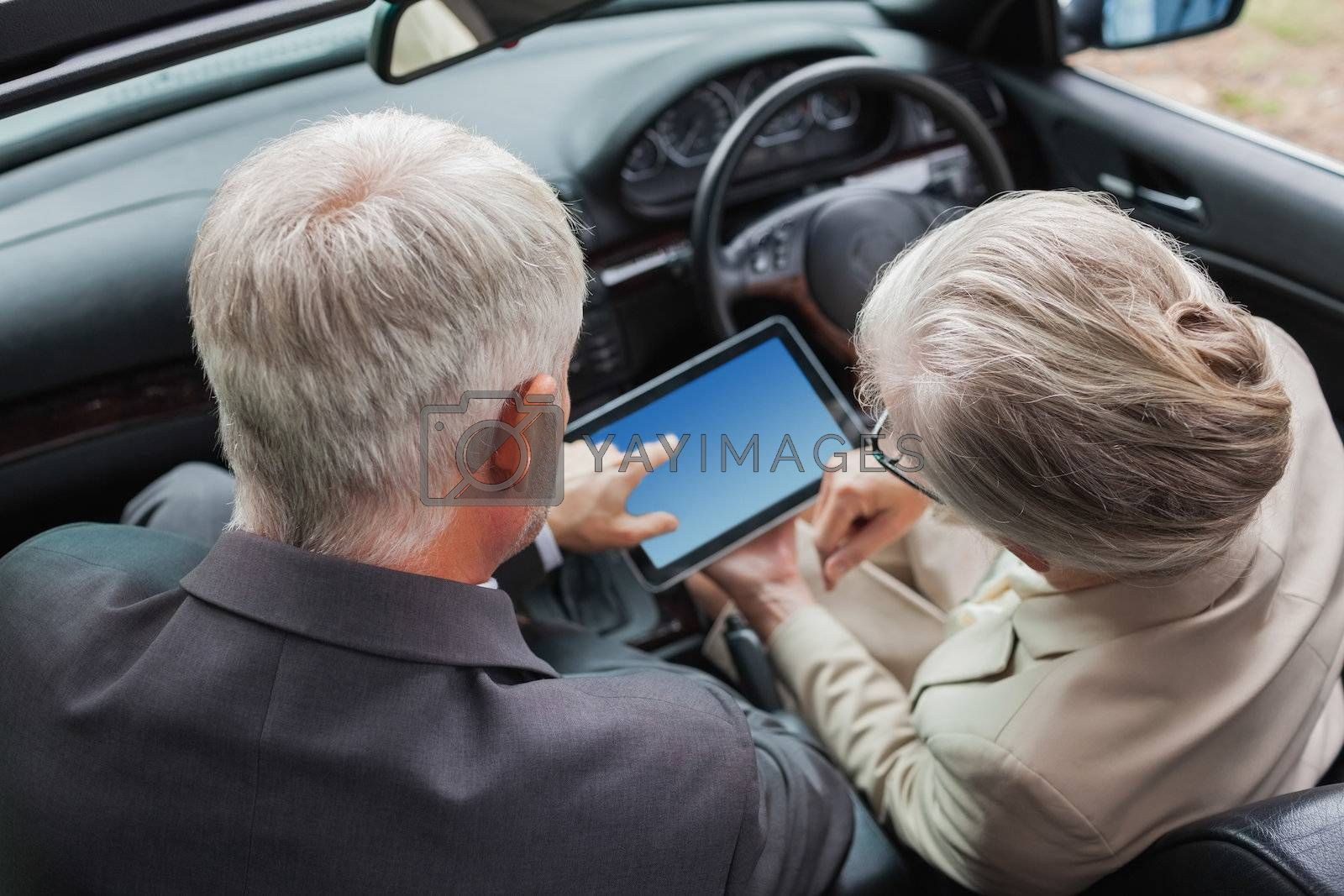 Mature partners working together on tablet in classy car by Wavebreakmedia