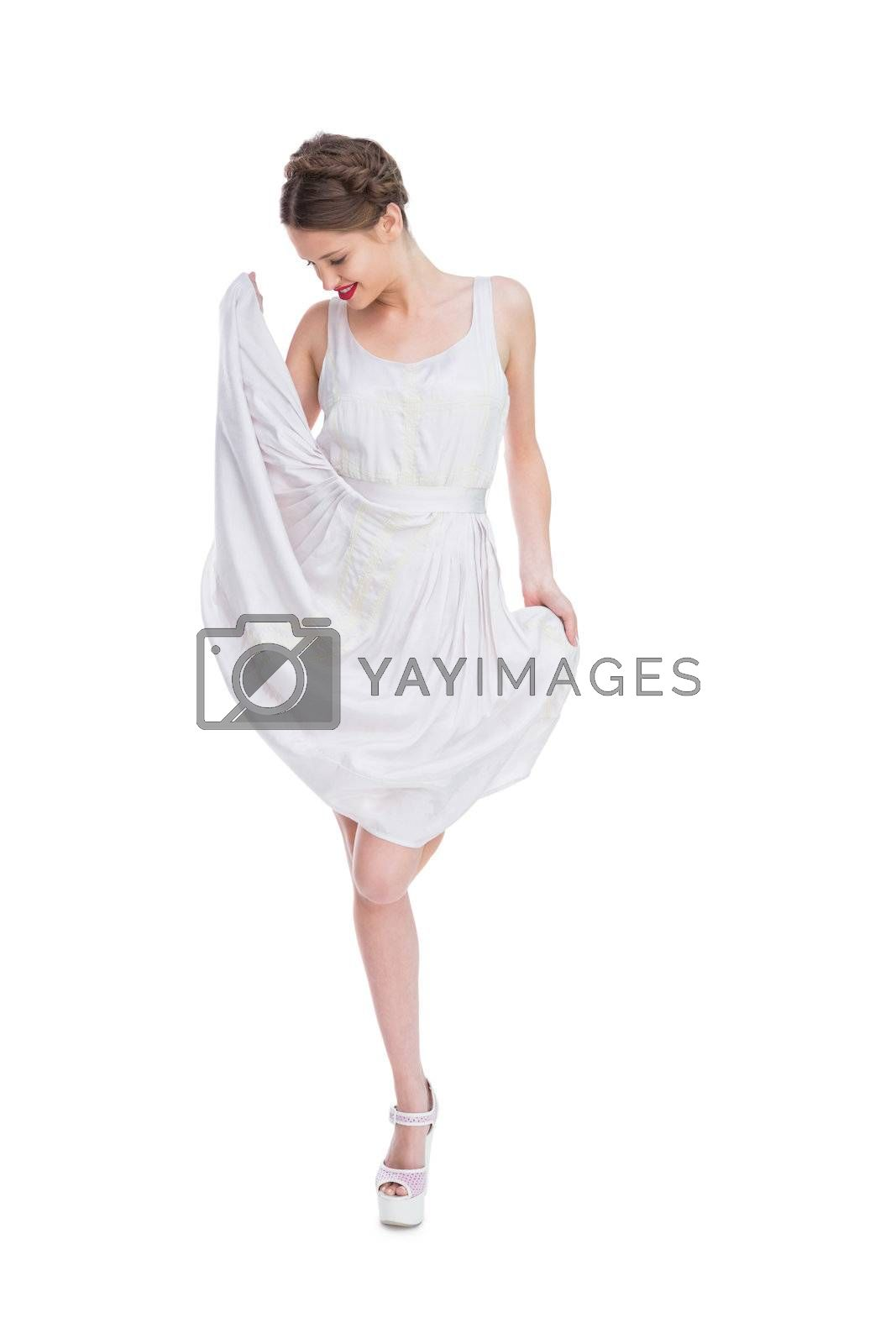 Smiling woman playing with her white summer dress by Wavebreakmedia
