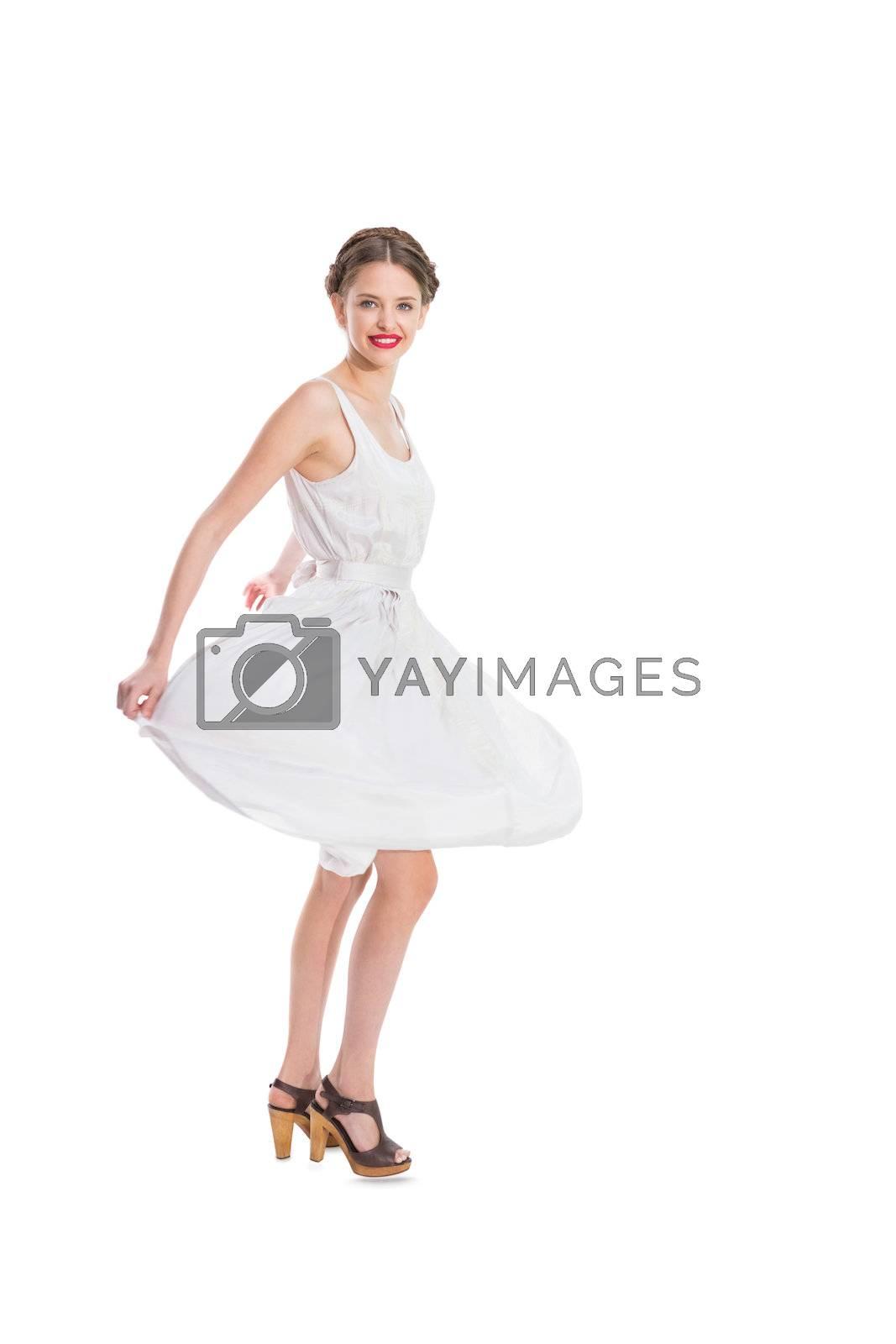 Happy pretty woman in white summer dress posing by Wavebreakmedia