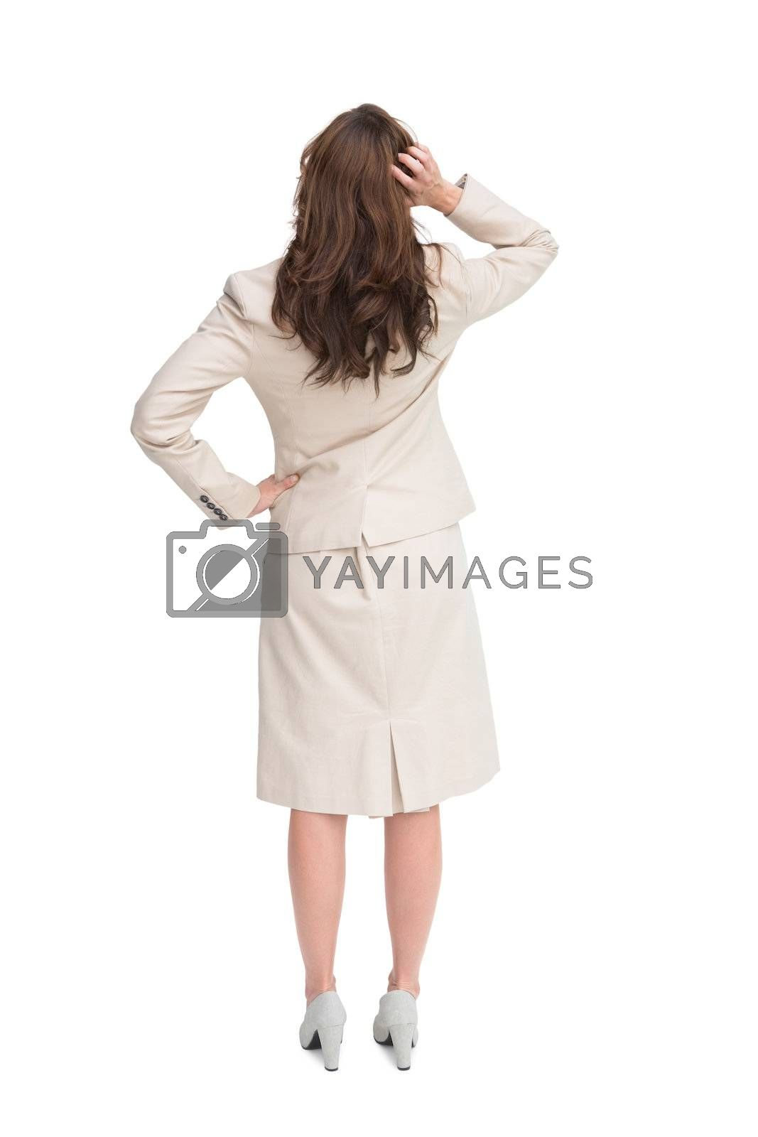 Businesswoman standing back to camera with hand on head by Wavebreakmedia