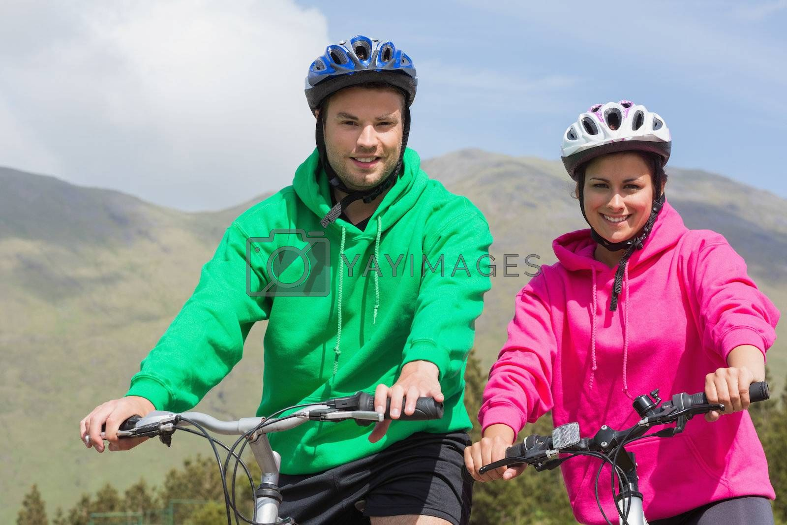 Smiling couple on a bike ride wearing hooded jumpers by Wavebreakmedia