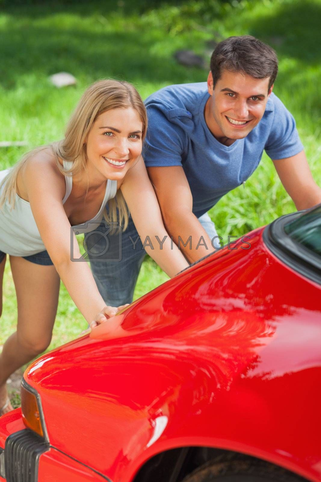 Smiling couple pushing their broken down car by Wavebreakmedia