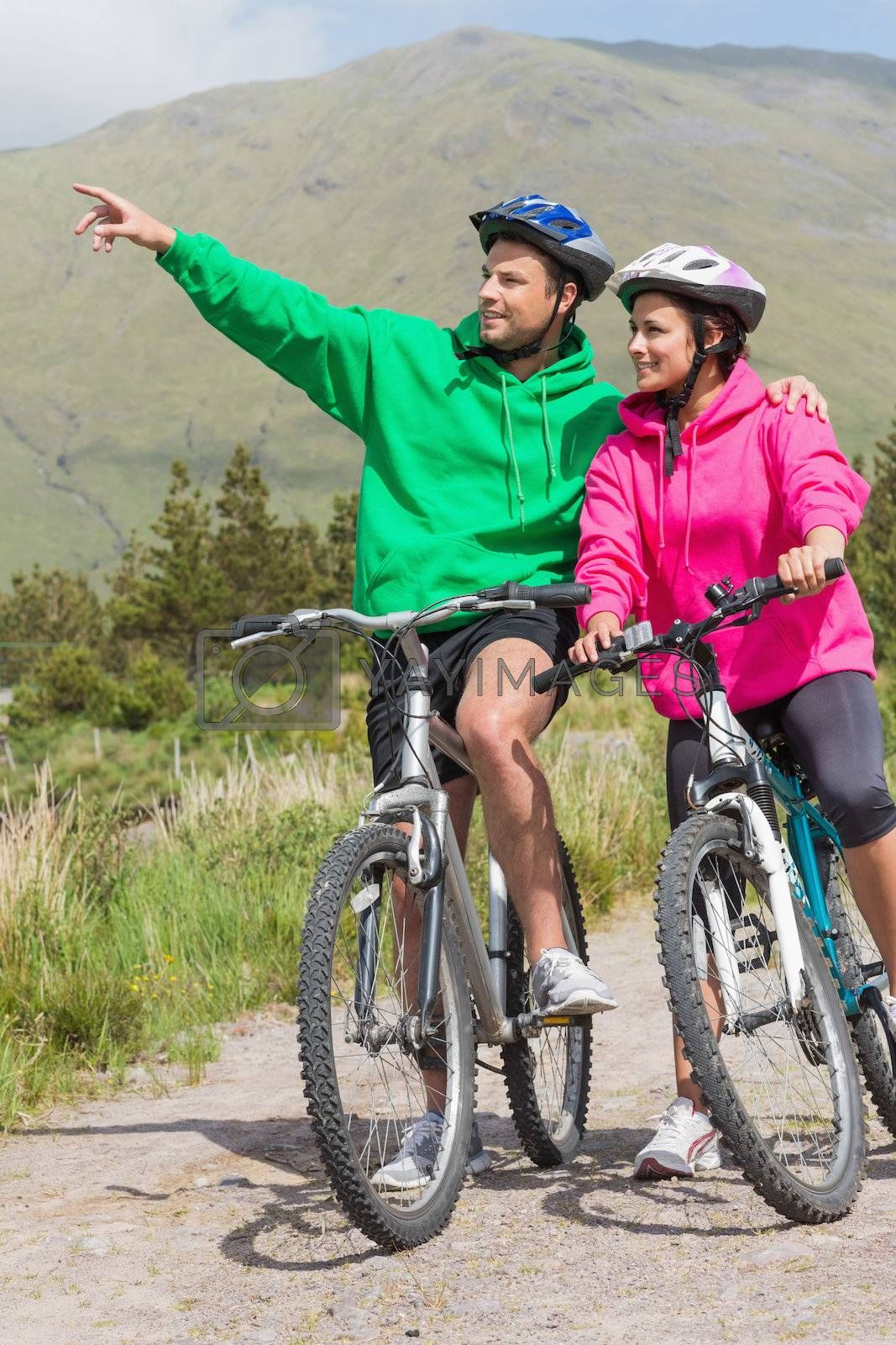 Athletic couple on a bike ride wearing hooded jumpers with man pointing by Wavebreakmedia