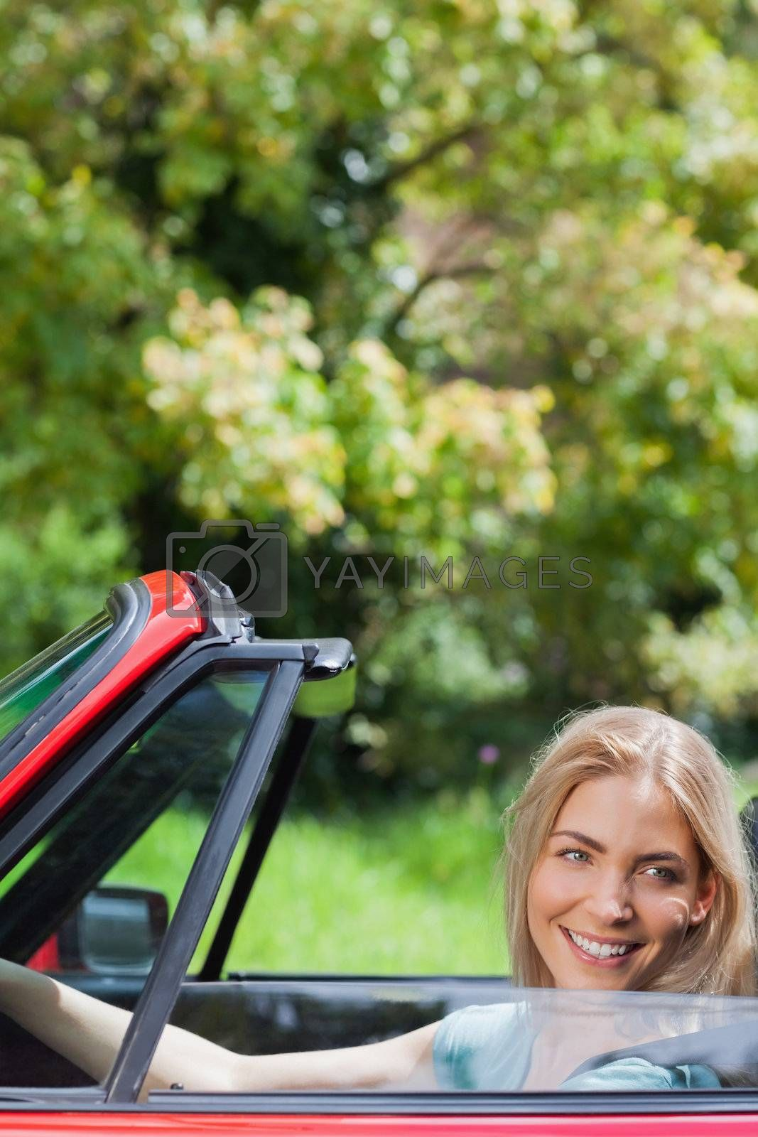 Happy blonde woman driving red cabriolet by Wavebreakmedia