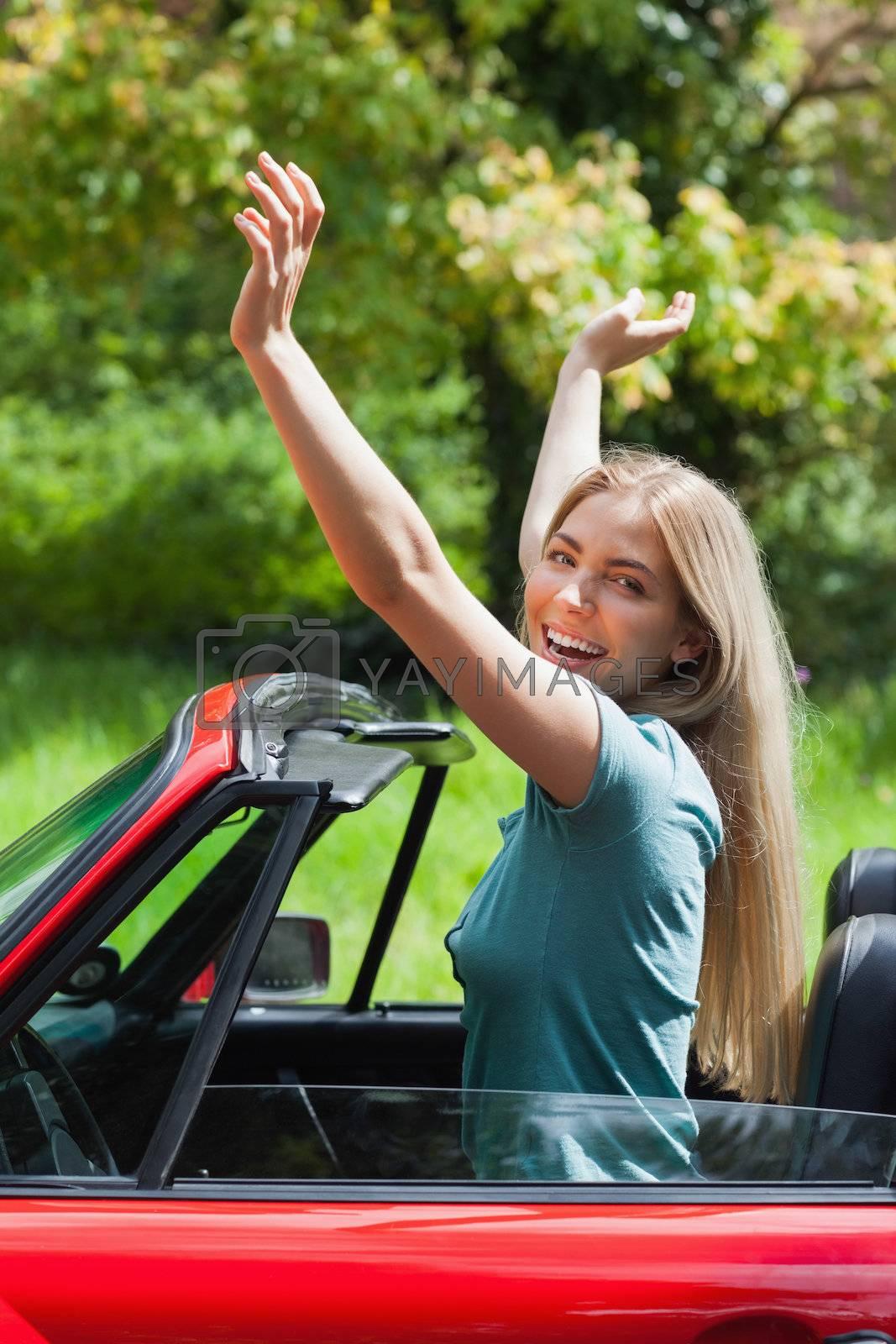 Smiling blonde enjoying her red cabriolet by Wavebreakmedia