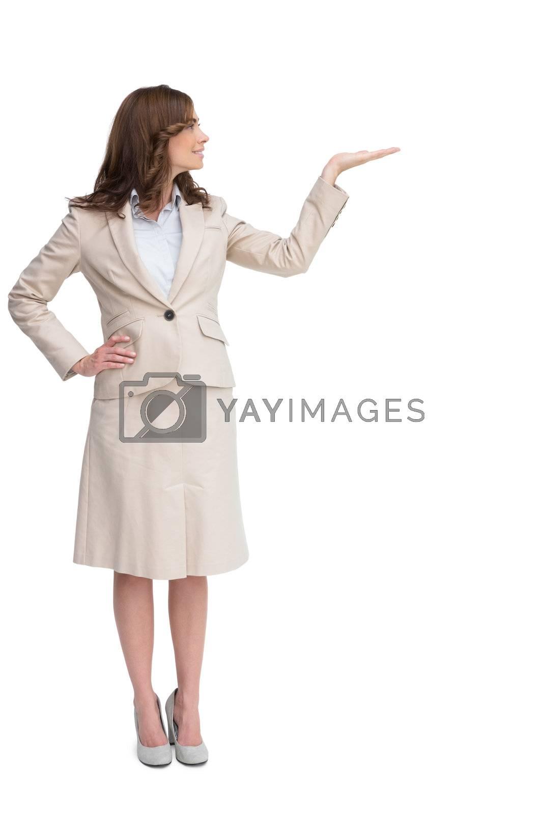 Smiling businesswoman raising her hand by Wavebreakmedia
