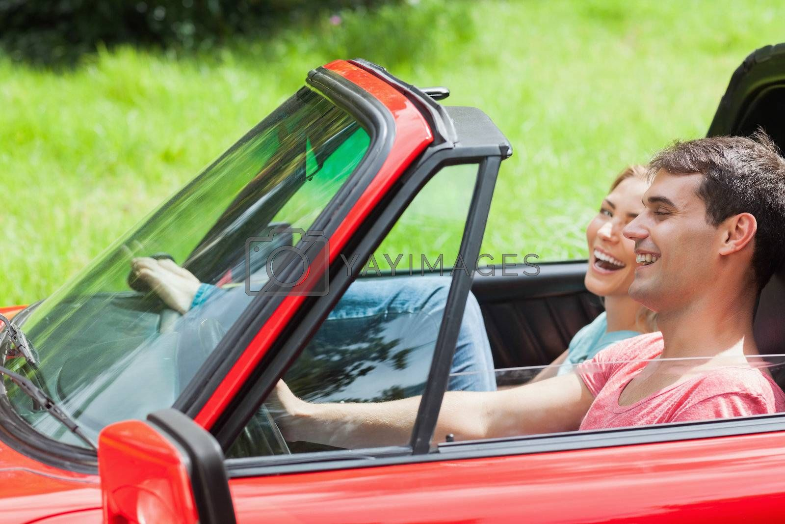 Smiling young couple having a ride in red cabriolet by Wavebreakmedia