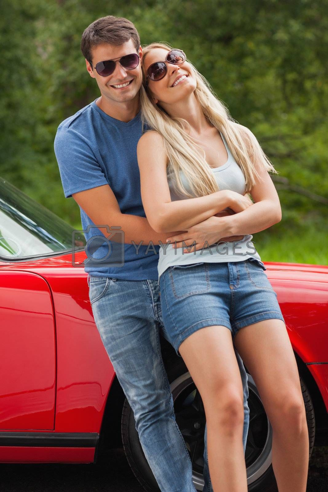 Loving couple hugging and leaning against cabriolet by Wavebreakmedia