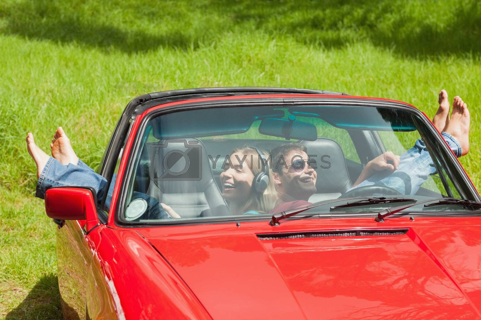 Smiling young couple relaxing in classy cabriolet by Wavebreakmedia