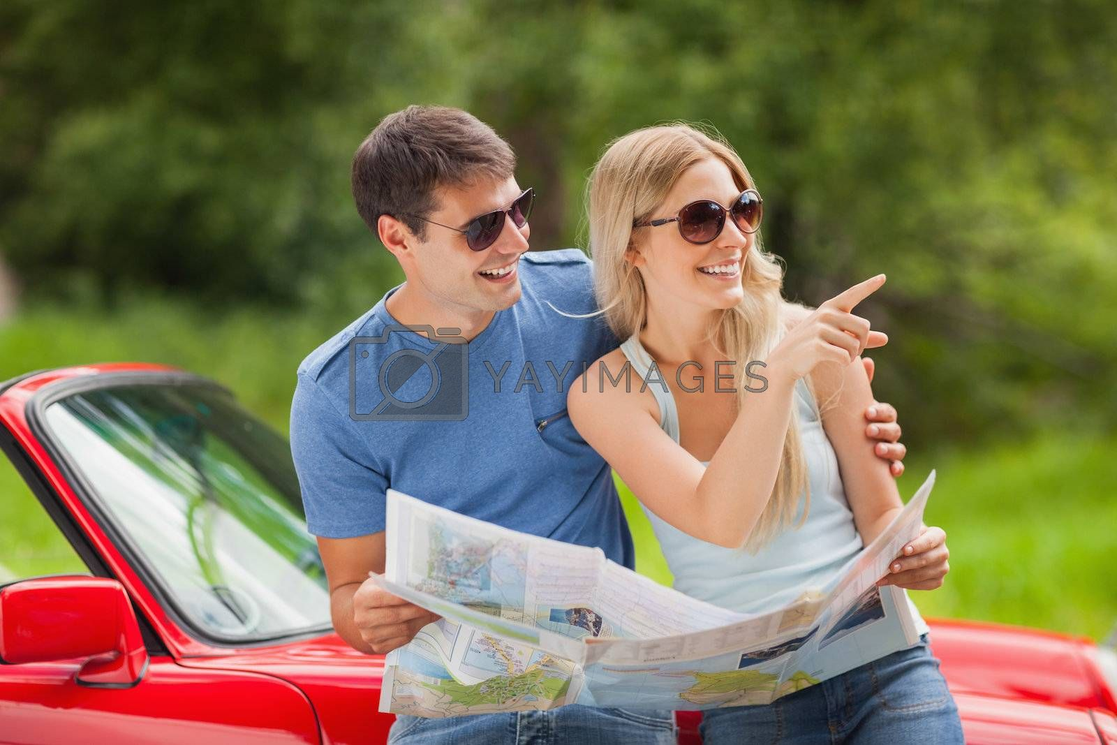 Cheerful young couple reading map by Wavebreakmedia